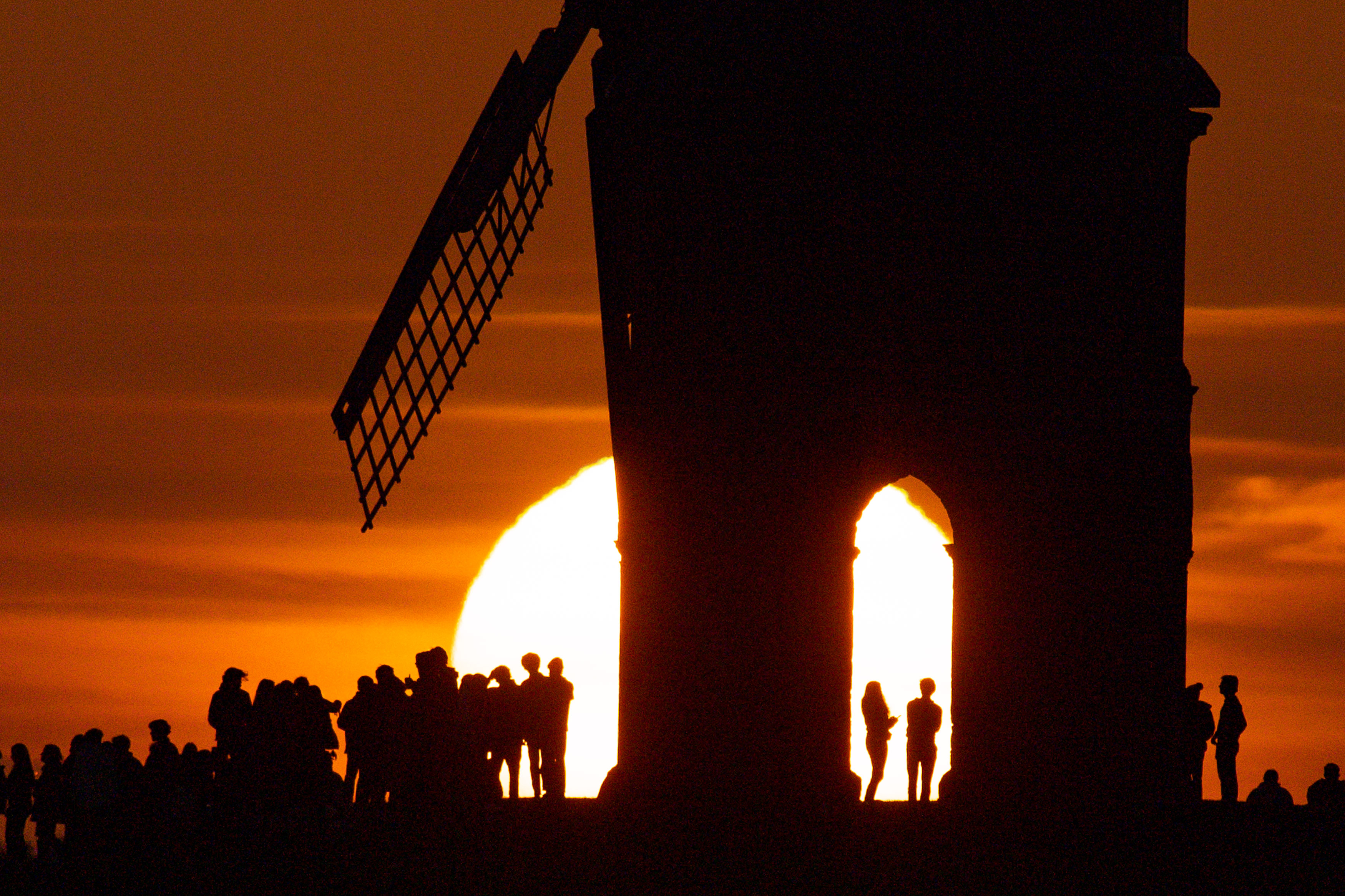 <p>Groups of people watch sunset by Chesterton Windmill in Warwickshire. Picture date: Wednesday March 17, 2021.</p>