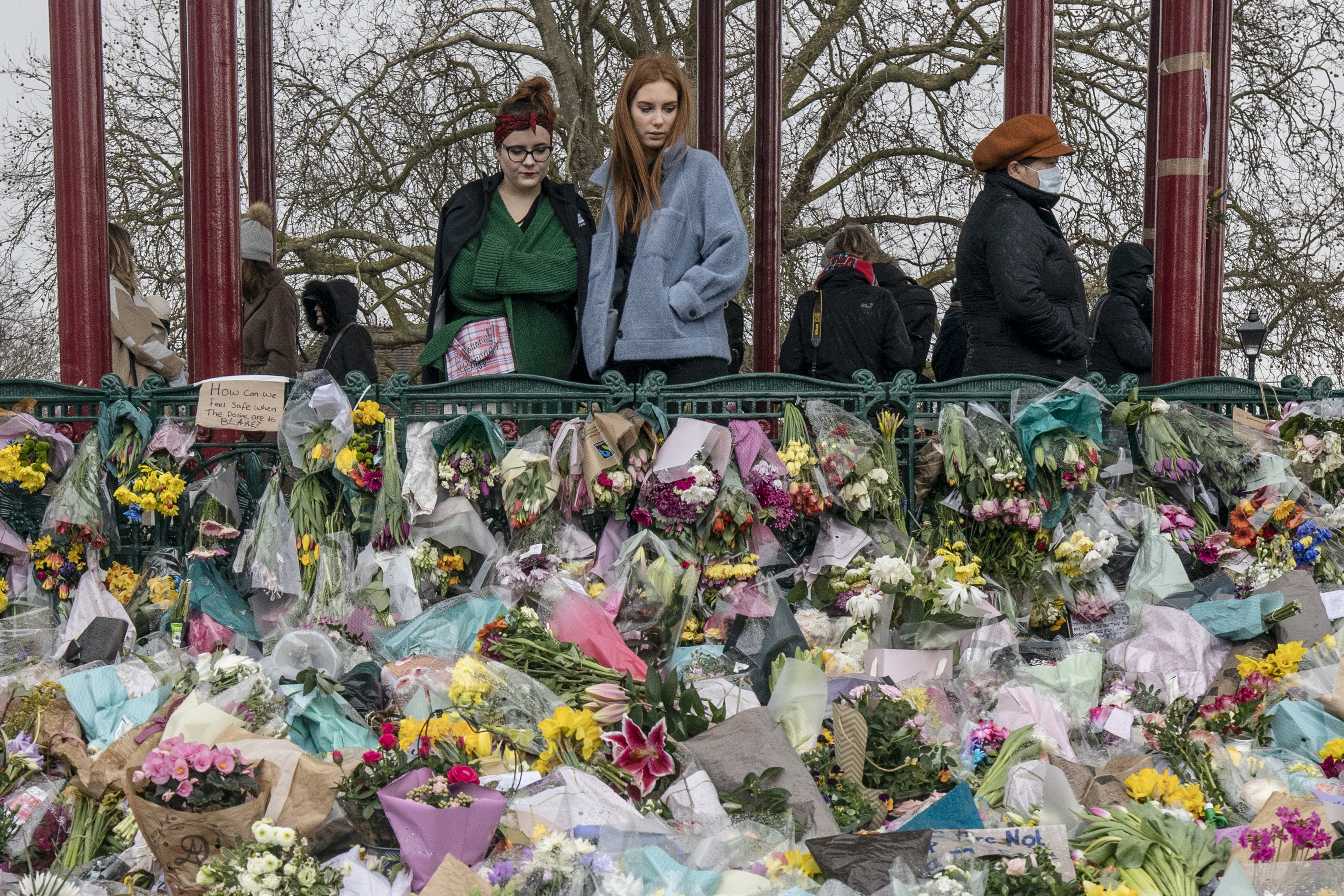 <p>LONDON, ENGLAND - MARCH 15: Well wishers look at the floral tributes placed in tribute to Sarah Everard on Clapham Common on March 15, 2021 in London, England. Hundreds of people turned out in Clapham Common on Saturday night to pay tribute to Sarah Everard, a 33-year-old London resident whose kidnapping and death - allegedly at the hands of an off-duty Metropolitan Police officer - prompted a wave of concern over women's safety. The same police force is being criticised for its response to the vigil, where they forcibly arrested several participants for violations of pandemic-era rules on public assembly. (Photo by Dan Kitwood/Getty Images)</p>