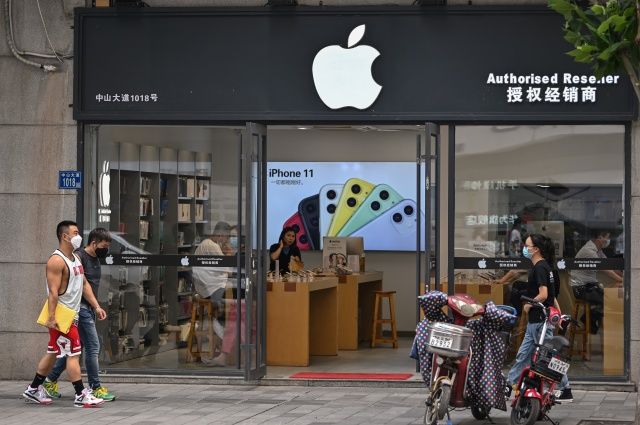 People wearing face masks walk past an Apple store in Wuhan, in Chinas central Hubei province on May 26, 2020. (Photo by Hector RETAMAL / AFP) (Photo by HECTOR RETAMAL/AFP via Getty Images)