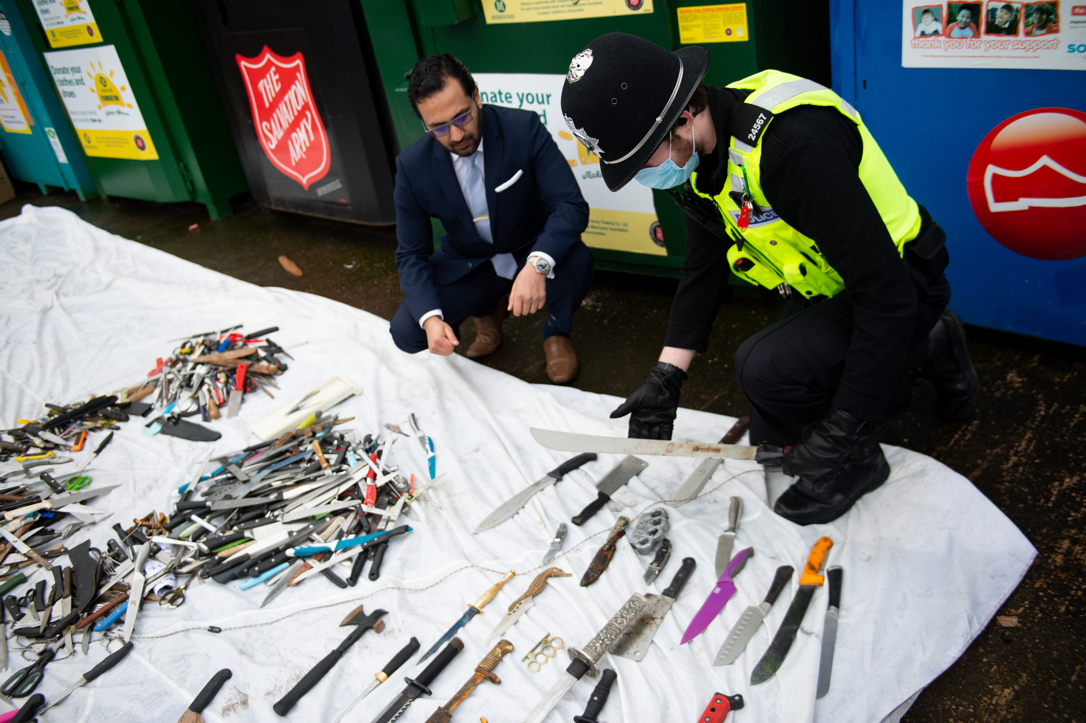 <p>West Midlands Deputy Police and Crime Commissioner, Waheed Saleem and a police officer showing the knives and other weapons that have been deposited into weapon surrender bins at Morrisons in Bilston, Wolverhampton. Picture date: Friday March 19, 2021.</p>