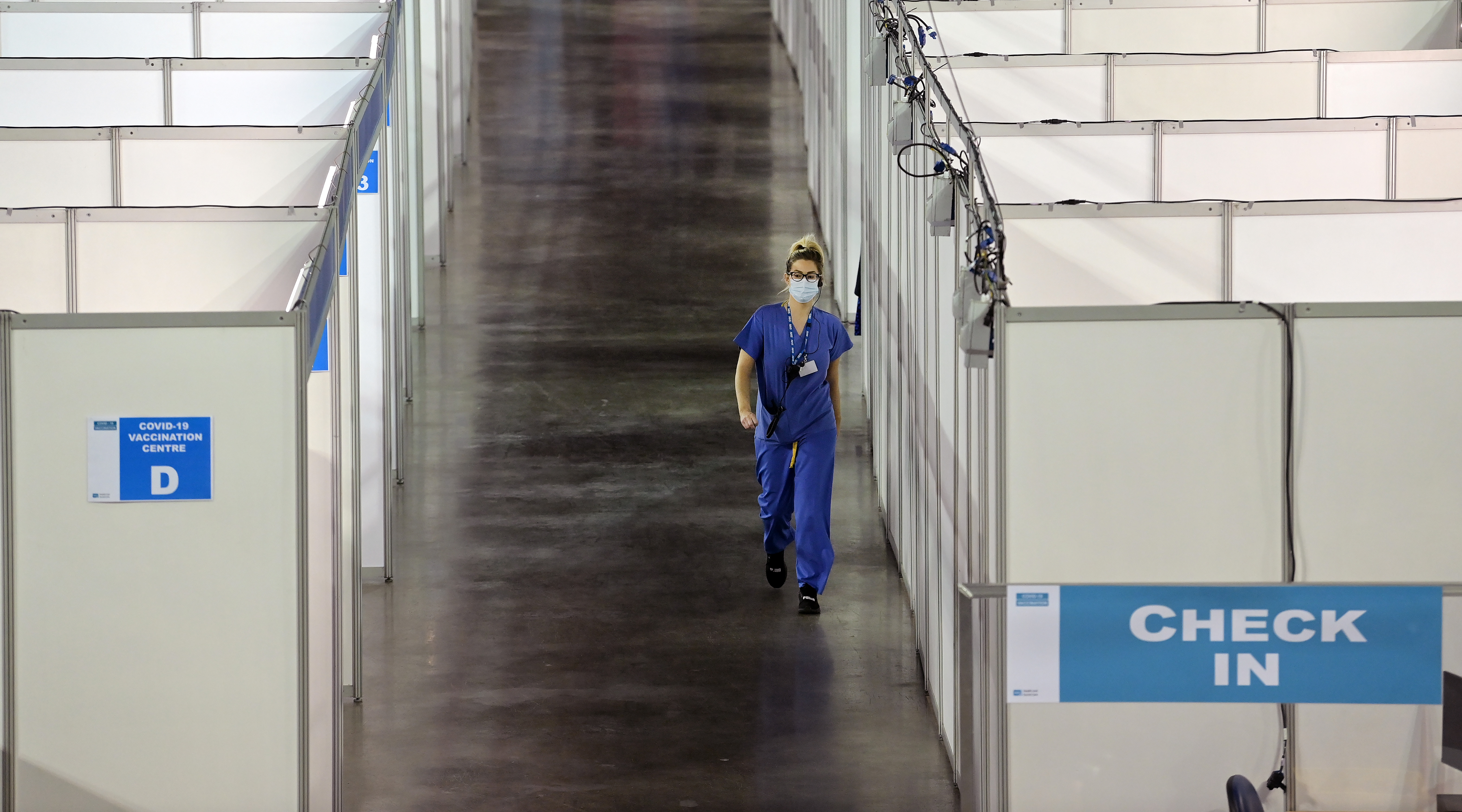 <p>BELFAST, NORTHERN IRELAND - MARCH 29: A vaccinator waits outside her cubicle as the provinces largest Covid-19 vaccination centre opens at the Odyssey SSE Arena on March 29, 2021 in Belfast, Northern Ireland. Northern Ireland, which has delivered at least one Covid-19 vaccine dose to about 38% of its overall population, slightly trails other UK nations in the inoculation campaign. But it's still significantly ahead of the Republic of Ireland, where just over 10 percent of its population has had the jab. (Photo by Charles McQuillan/Getty Images)</p>