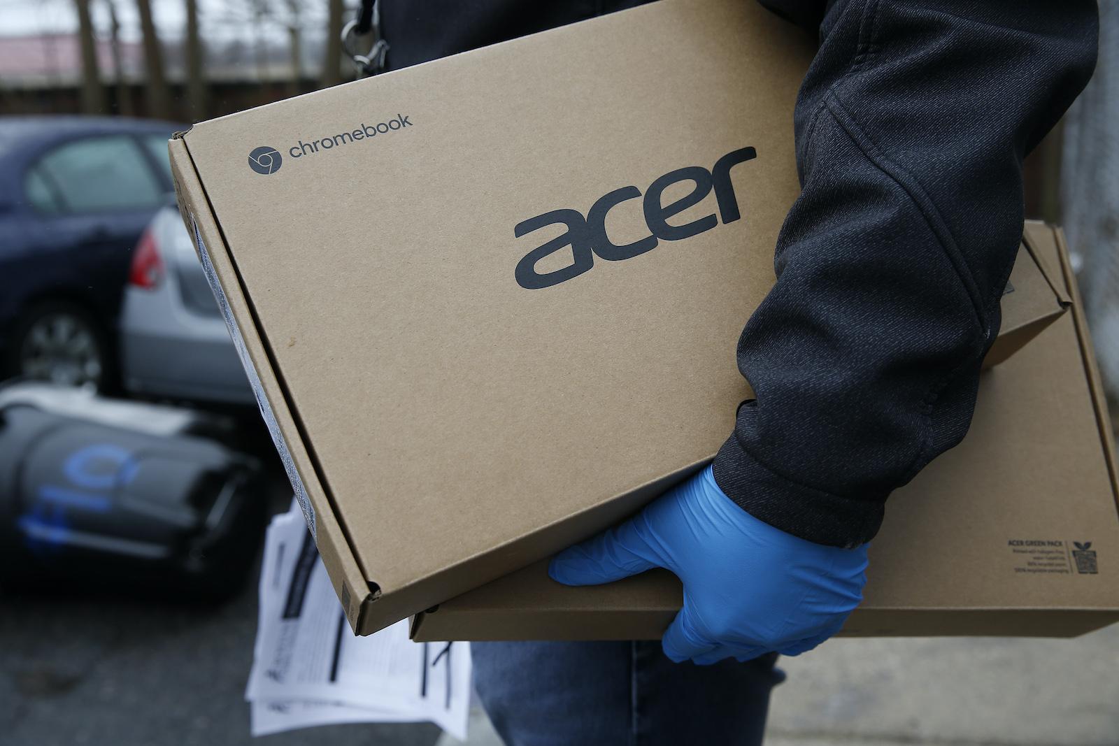 波士頓,馬薩諸塞州-3月19日:波士頓公立學校員工Giscar Centeio持有兩台筆記本電腦,因為他會在2020年3月19日在波士頓向學生分發Acer chromebooks的空運行去門口。馬薩諸塞州的學校已經關閉以阻止冠狀病毒的傳播。  (照片由傑西卡·里納爾迪(Jessica Rinaldi)/《波士頓環球報》通過蓋蒂圖片社提供)