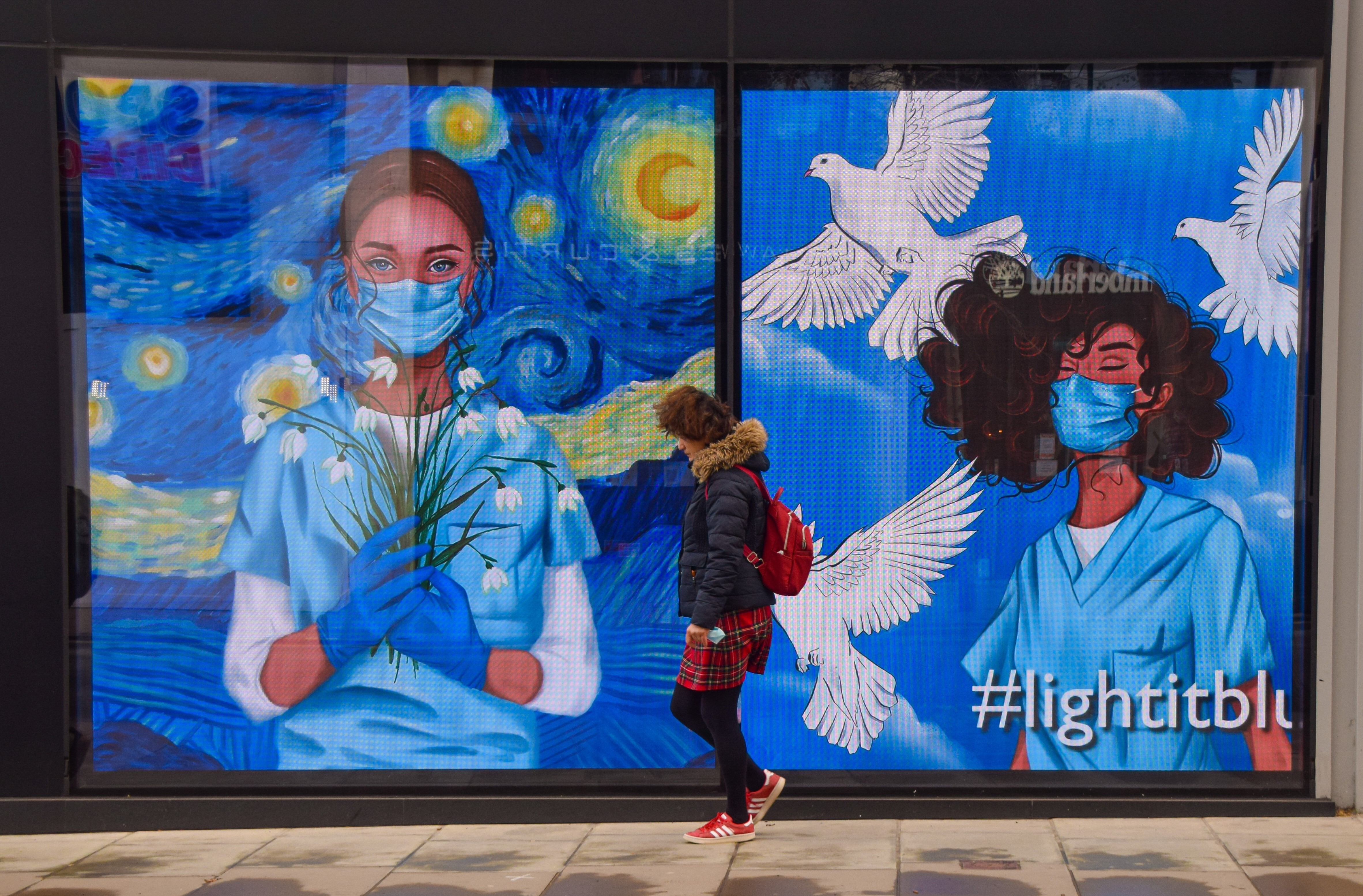 <p>A woman walks past the screens displaying medical workers wearing face masks at the Flannels store on Oxford Street in London. The screens at the store were showing a series of artworks as part of the 'Light It Blue' campaign in support of the NHS during the coronavirus crisis. (Photo by Vuk Valcic / SOPA Images/Sipa USA)</p>