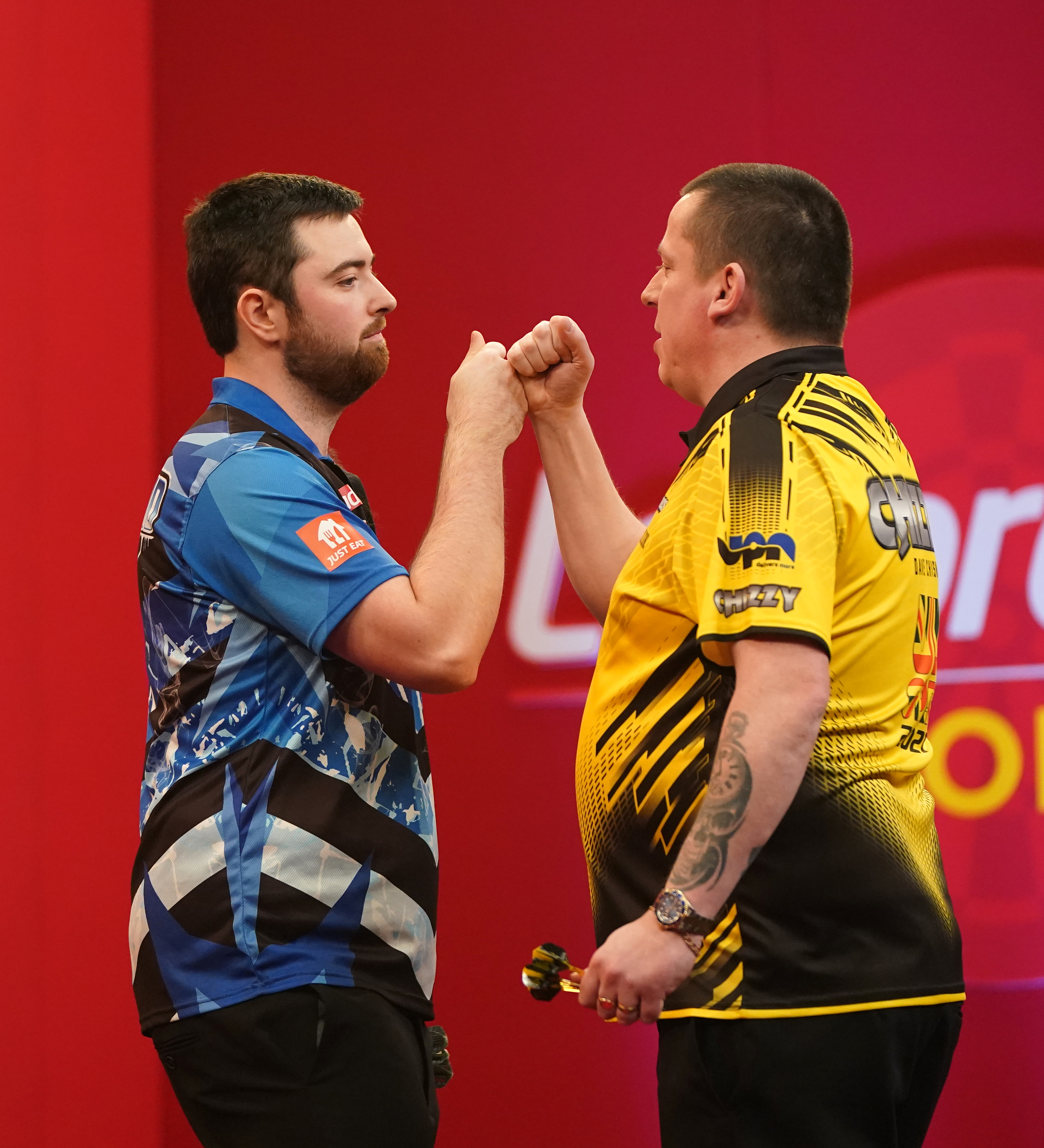 <p>Dave Chisnall (right) congratulates Luke Humphries during day three of the Ladbrokes UK Open 2021 tournament at the Marshall Arena, Milton Keynes. Picture date: Sunday March 7, 2021.</p>