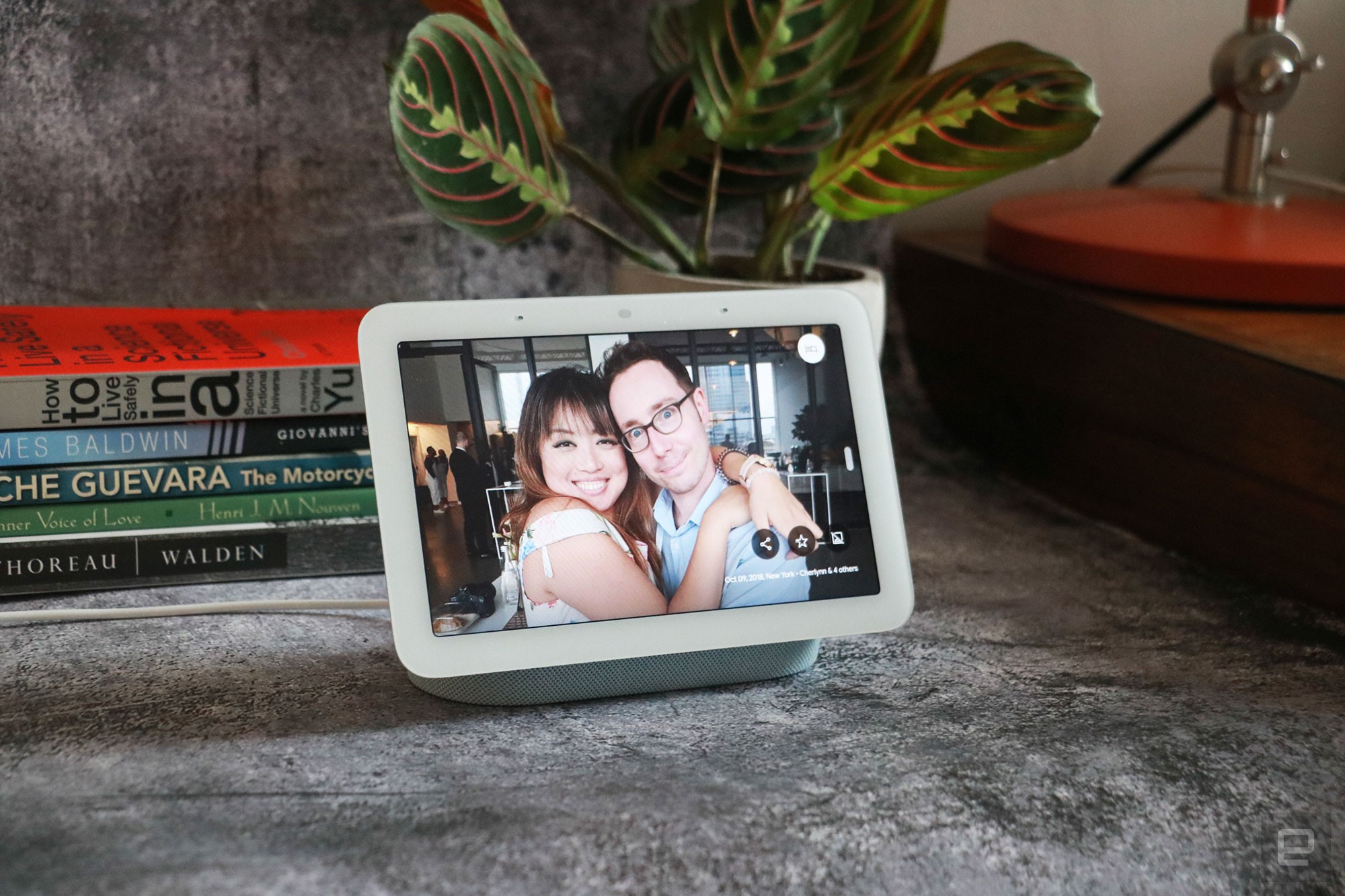 <p>Google Nest Hub 2021 (2nd gen) photo. Picture of Google's newest smart display on a table with books and a plant in the background.</p>