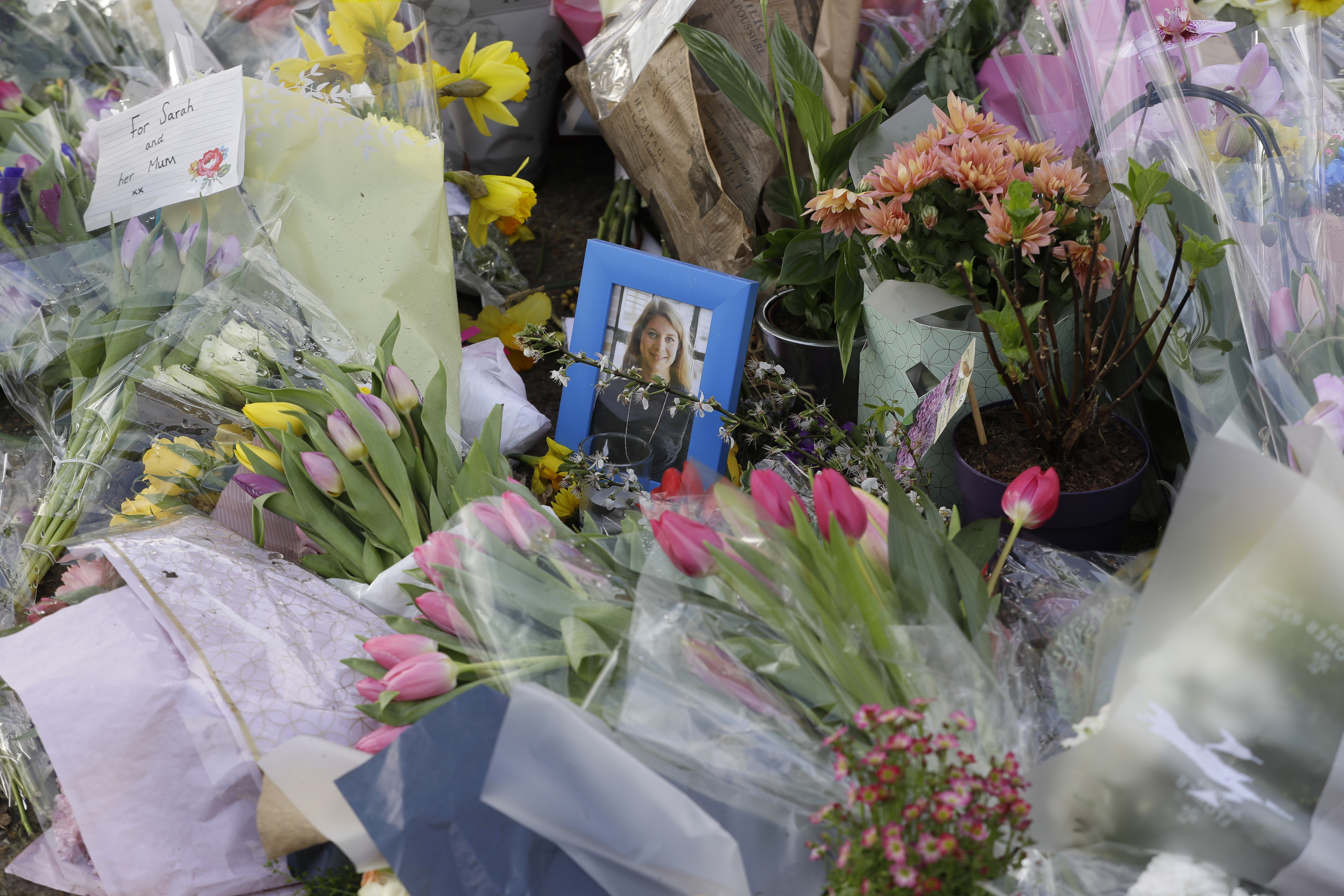 <p>A photograph of Sarah Everard amongst floral tributes and candles placed at the bandstand on Clapham Common, London, Monday March 15, 2021. On Saturday hundreds of people disregarded a judge's ruling and police requests by gathering at Clapham Common in honor of Sarah Everard. Everard disappeared while walking home from a friend's apartment and was found dead a week later. The slaying sent shockwaves across the U.K. because a Metropolitan Police officer is charged with her kidnapping and murder. (AP Photo/Kirsty Wigglesworth)</p>