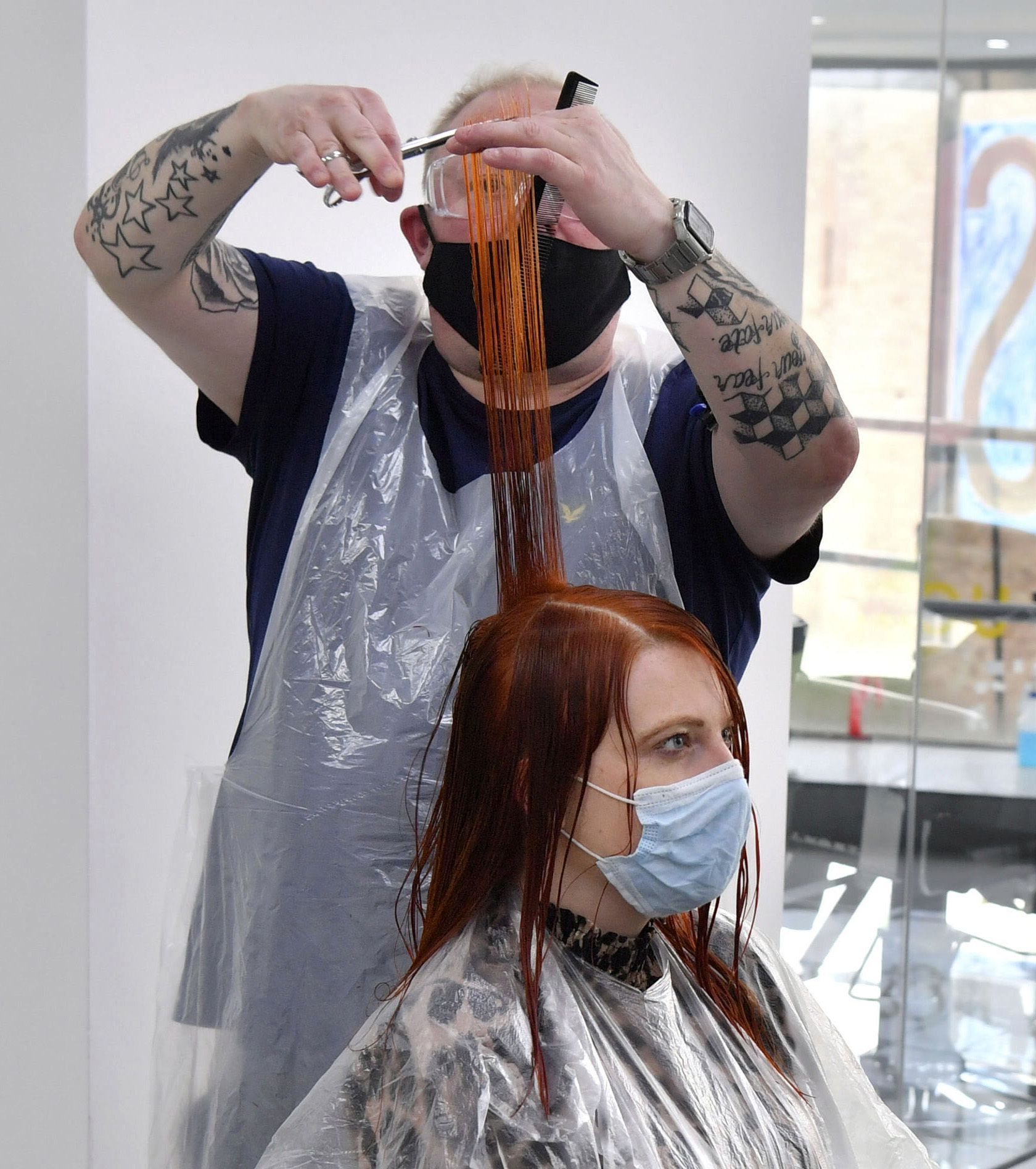 <p>A stylist cuts the hair of a client at the Lazarou salon in Cardiff, Wales, Monday March 15, 2021. Hairdressers and barbers in Wales can reopen from Monday, as coronavirus restrictions are eased, marking the first lifting of rules for close contact services. (Ben Birchall/PA via AP)</p>