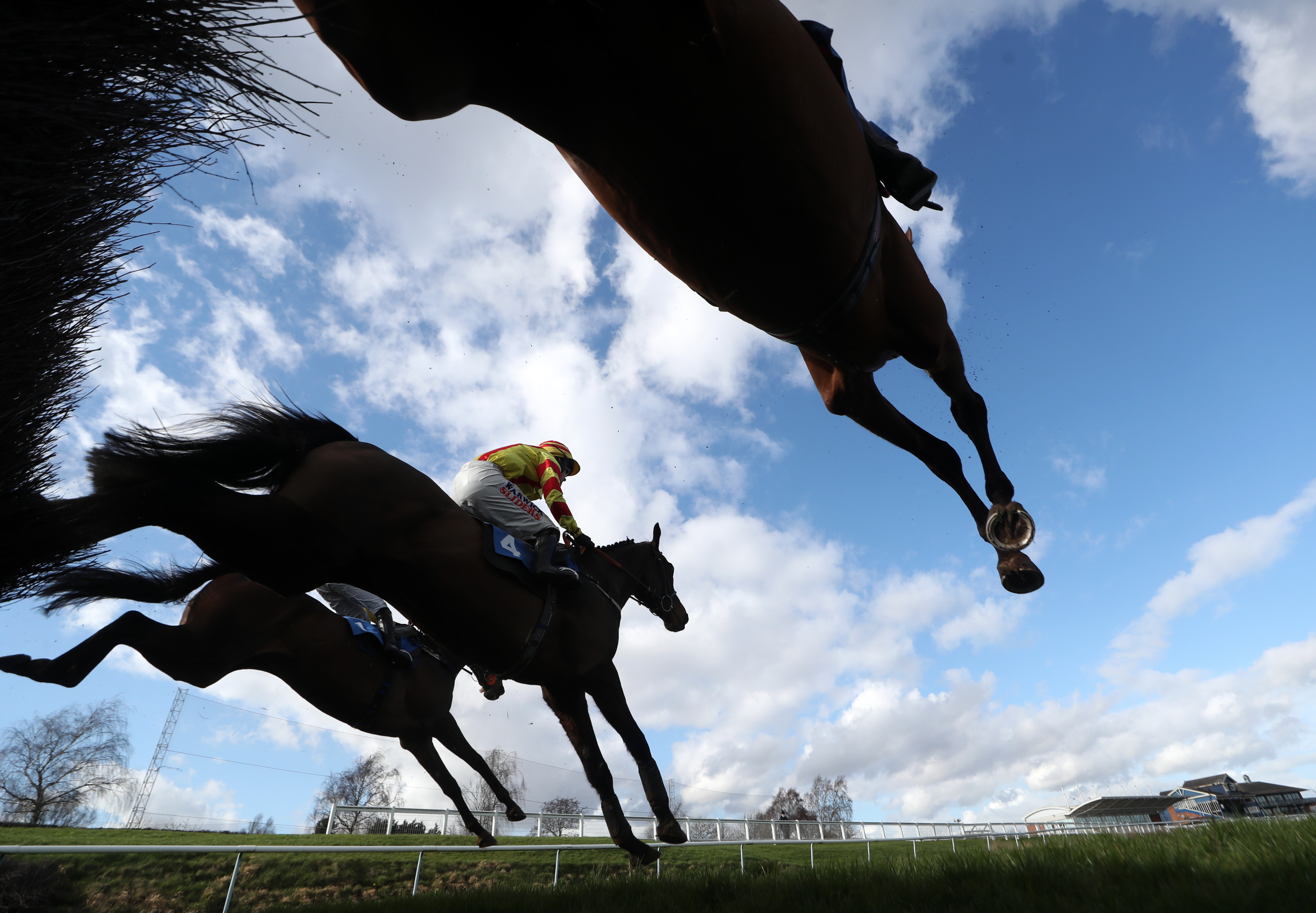 <p>Runner and riders clear a fence during the Racing TV Profits Returned To Racing Handicap Chase at Leicester Racecourse. Picture date: Friday March 12, 2021.</p>