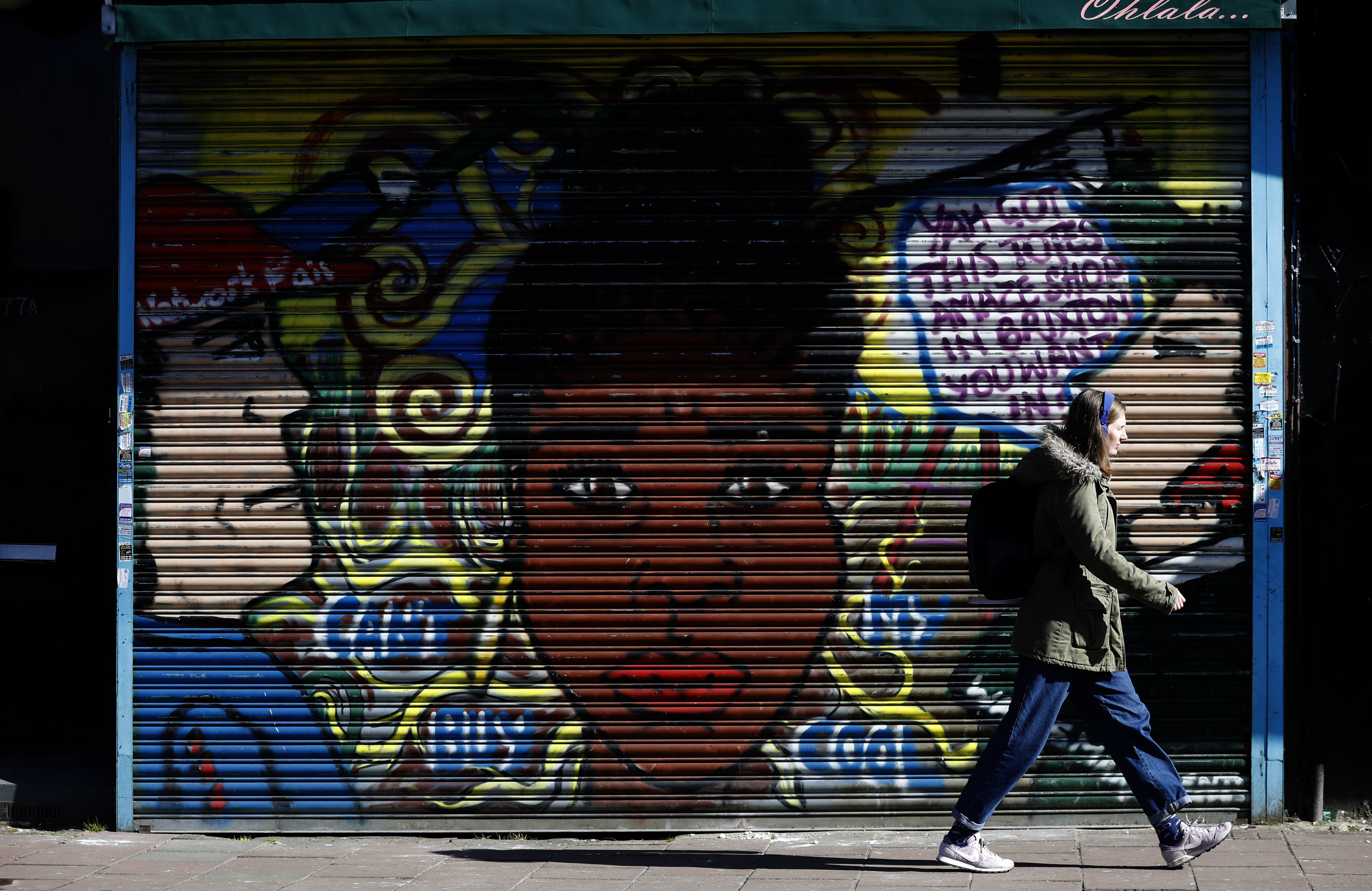 <p>A woman walks past a mural in Brixton in London, Tuesday, March 9, 2021. (AP Photo/Alastair Grant)</p>