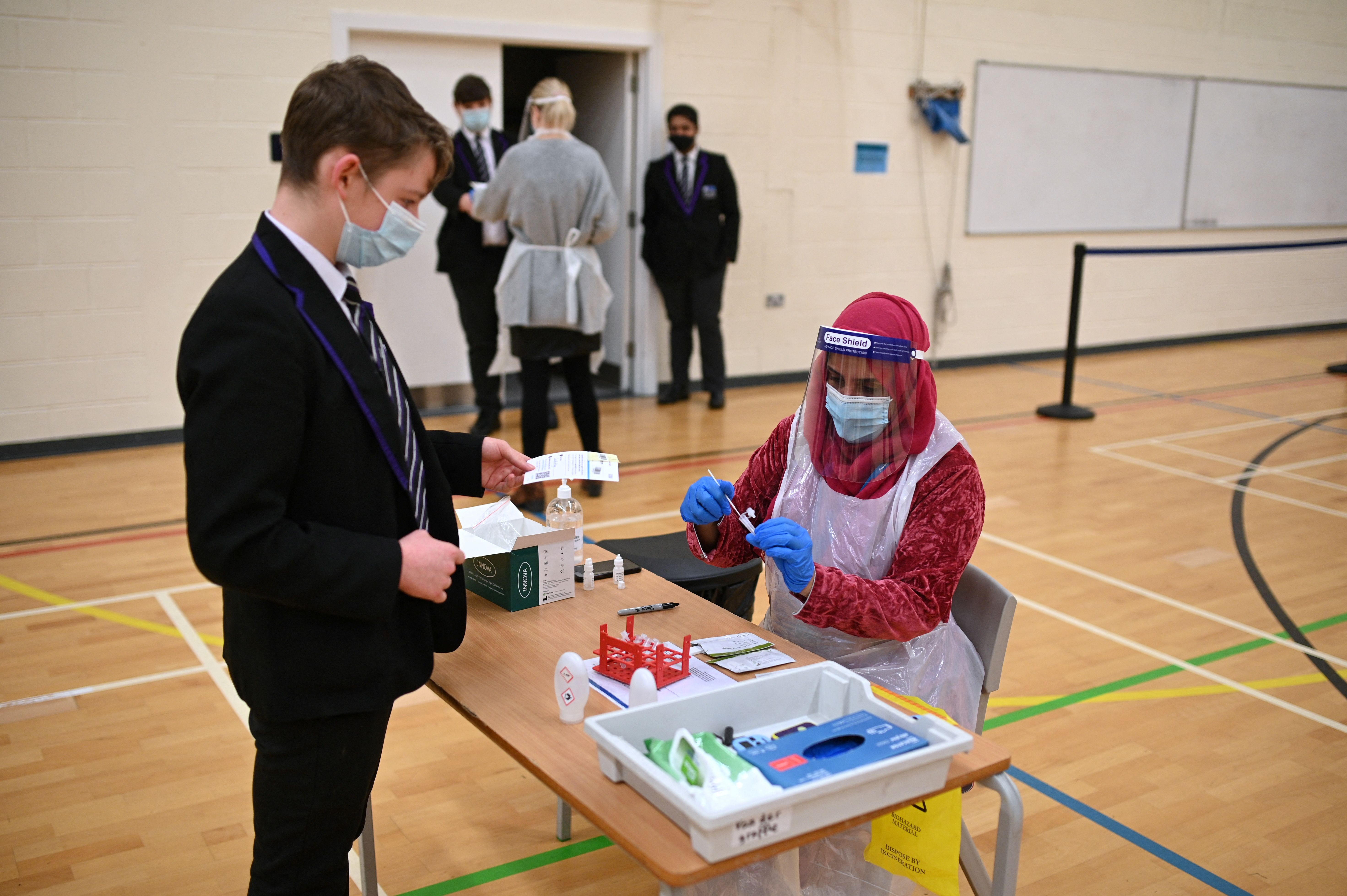 <p>Year 10 students hand over completed lateral flow Covid-19 tests to staff in the Sports Hall at Park Lane Academy in Halifax, northwest England on March 17, 2021. (Photo by Oli SCARFF / AFP) (Photo by OLI SCARFF/AFP via Getty Images)</p>