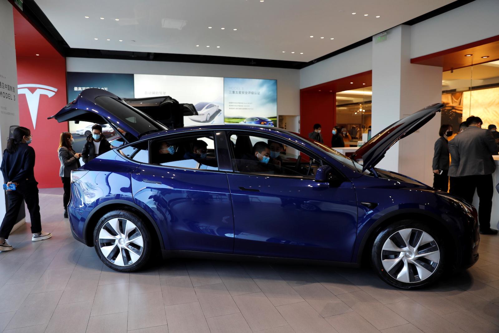 戴著口罩的訪客在2021年1月5日在中國北京的電動汽車製造商的陳列室裡檢查了特斯拉Y型運動型多功能車(SUV)。路透社/王廷樹-RC2K1L98RI0T