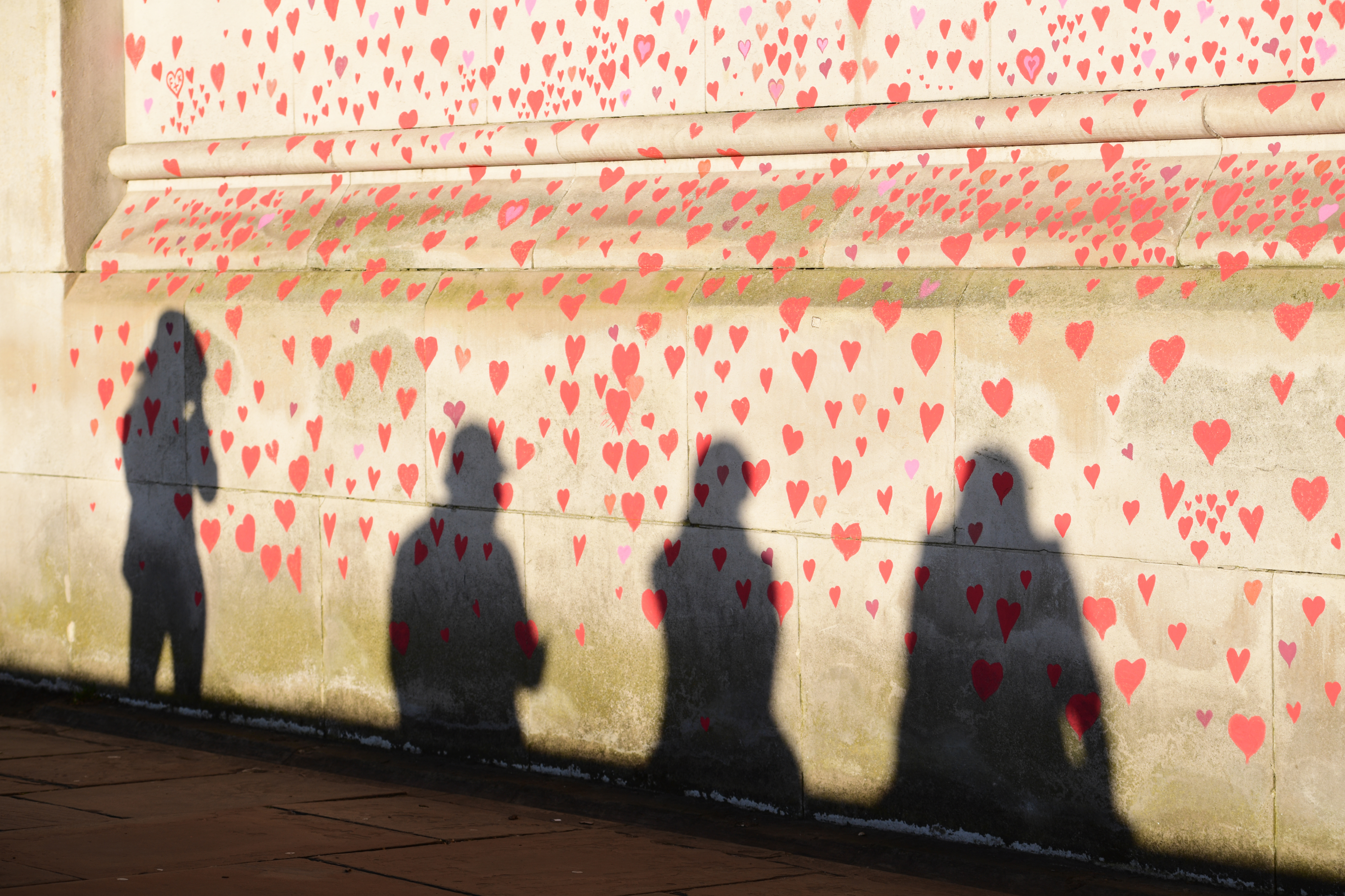 <p>People are silhouetted against the COVID-19 Memorial Wall on the Embankment, central London, which has been painted with hearts in memory of the more than 145,000 people who have died in the UK from coronavirus. Picture date: Monday March 29, 2021.</p>