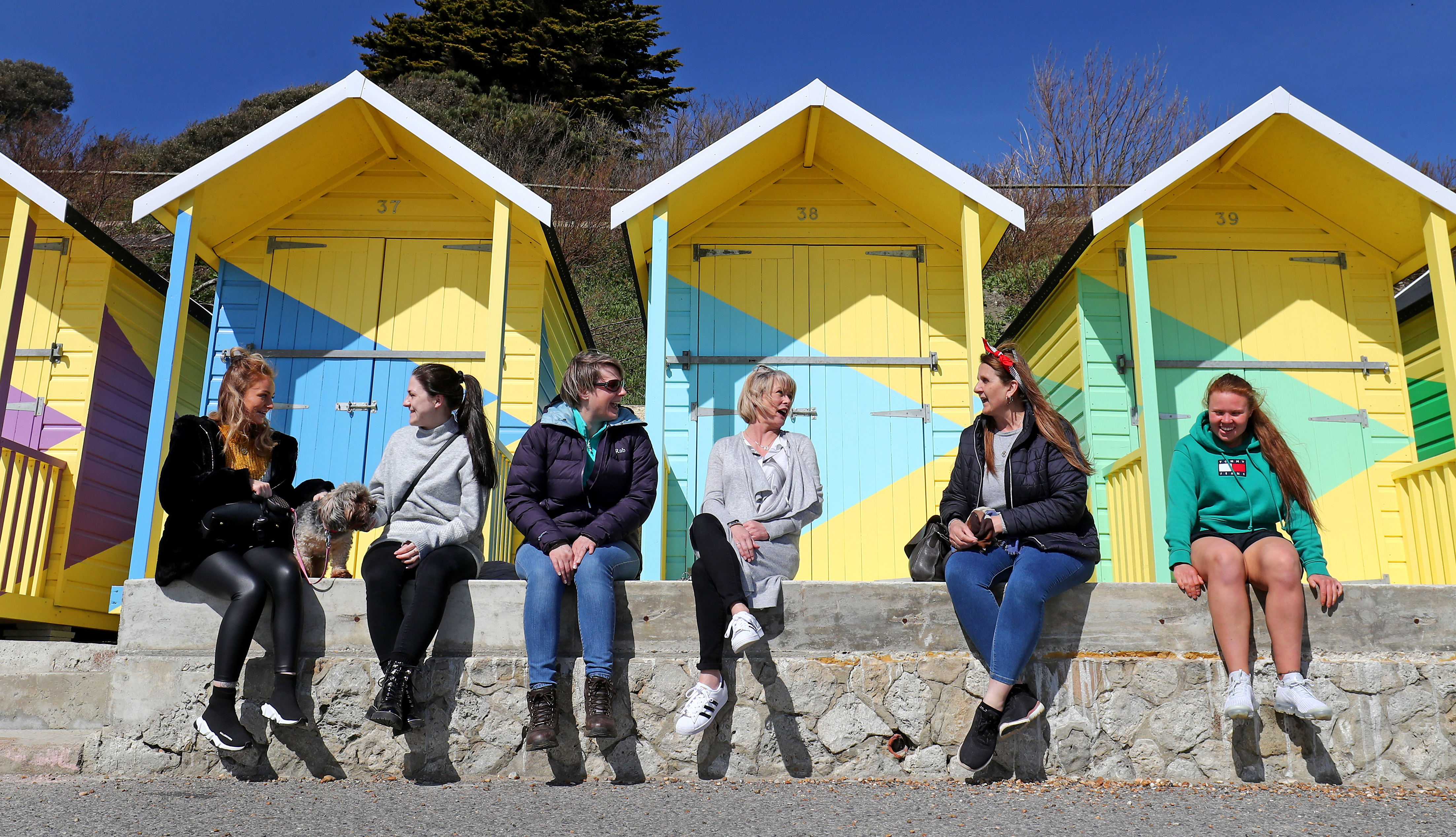 <p>A group of work colleagues pause for a chat during a walk along the promenade in Folkestone, Kent, following the easing of England's lockdown to allow far greater freedom outdoors. Picture date: Monday March 29, 2021.</p>