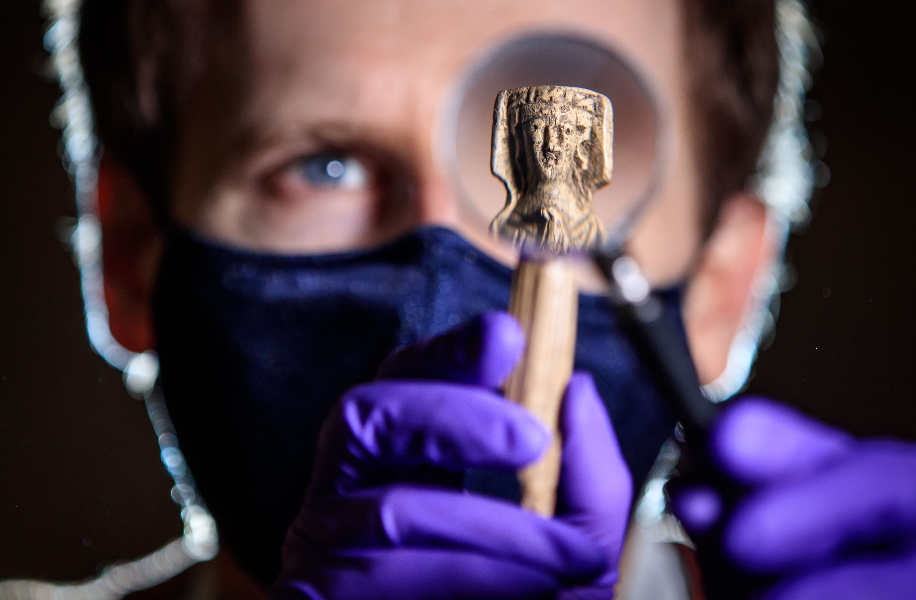 <p>Andrew Woods, senior curator at the Yorkshire Museum, holds a magnifying glass in front of a medieval bone handle carving of a woman dressed in a gown and headdress, dating to the 14th Century, one of thousands of artefacts in the care of York Museums Trust that are being photographed and put online for the public to view, while the museum in York remains closed during England's third national lockdown to curb the spread of coronavirus. Picture date: Wednesday March 10, 2021. (Photo by Danny Lawson/PA Images via Getty Images)</p>
