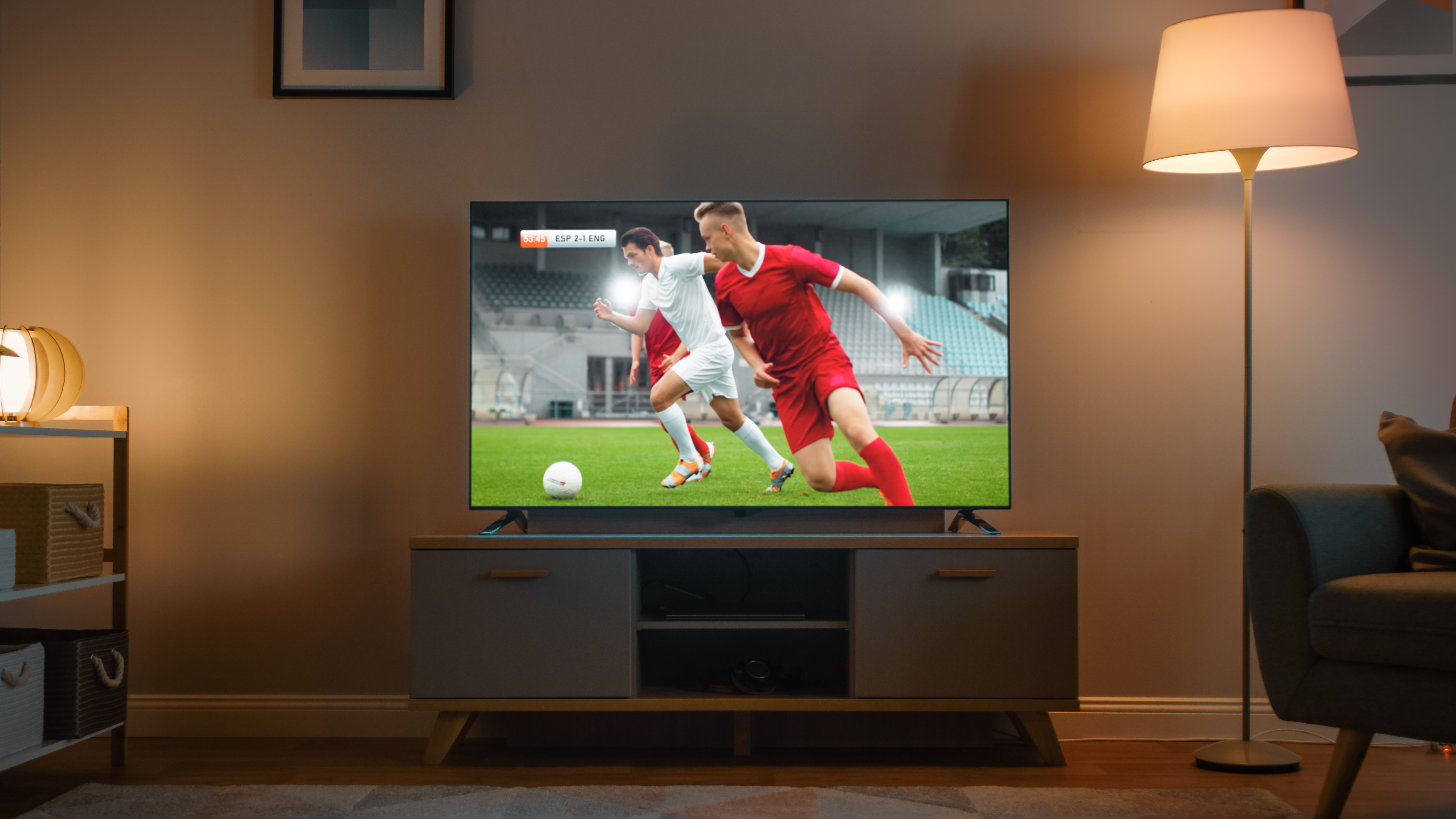 Shot of a TV with Soccer Match. Cozy Evening Living Room with a Chair and Lamps Turned On at Home.