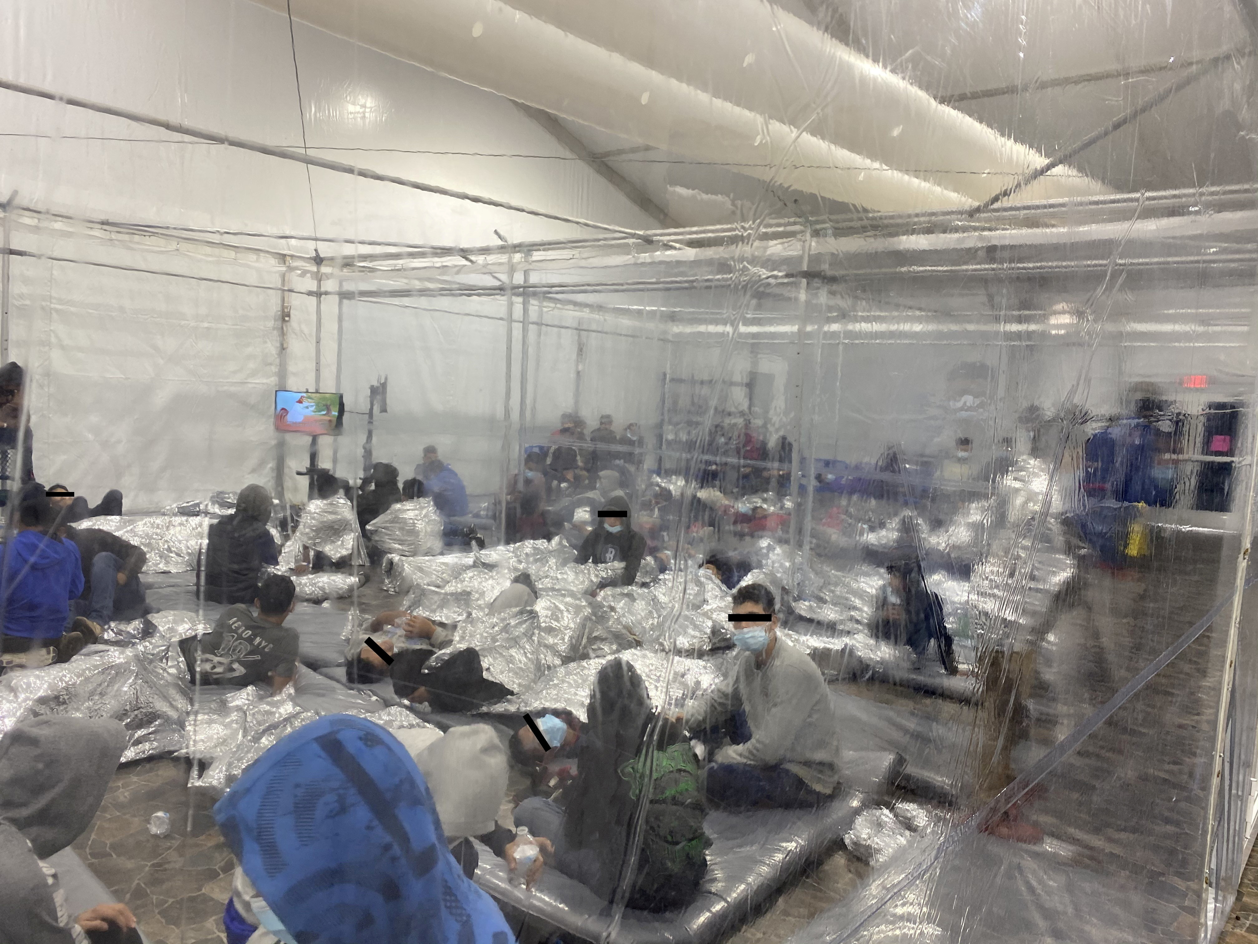 A photograph released by the office of Rep. Henry Cuellar, D-Texas, shows migrants crowded in a room with walls of plastic sheeting at the U.S. Customs and Border Protection temporary processing center in Donna, Texas on March 22, 2021 (Handout via Reuters).