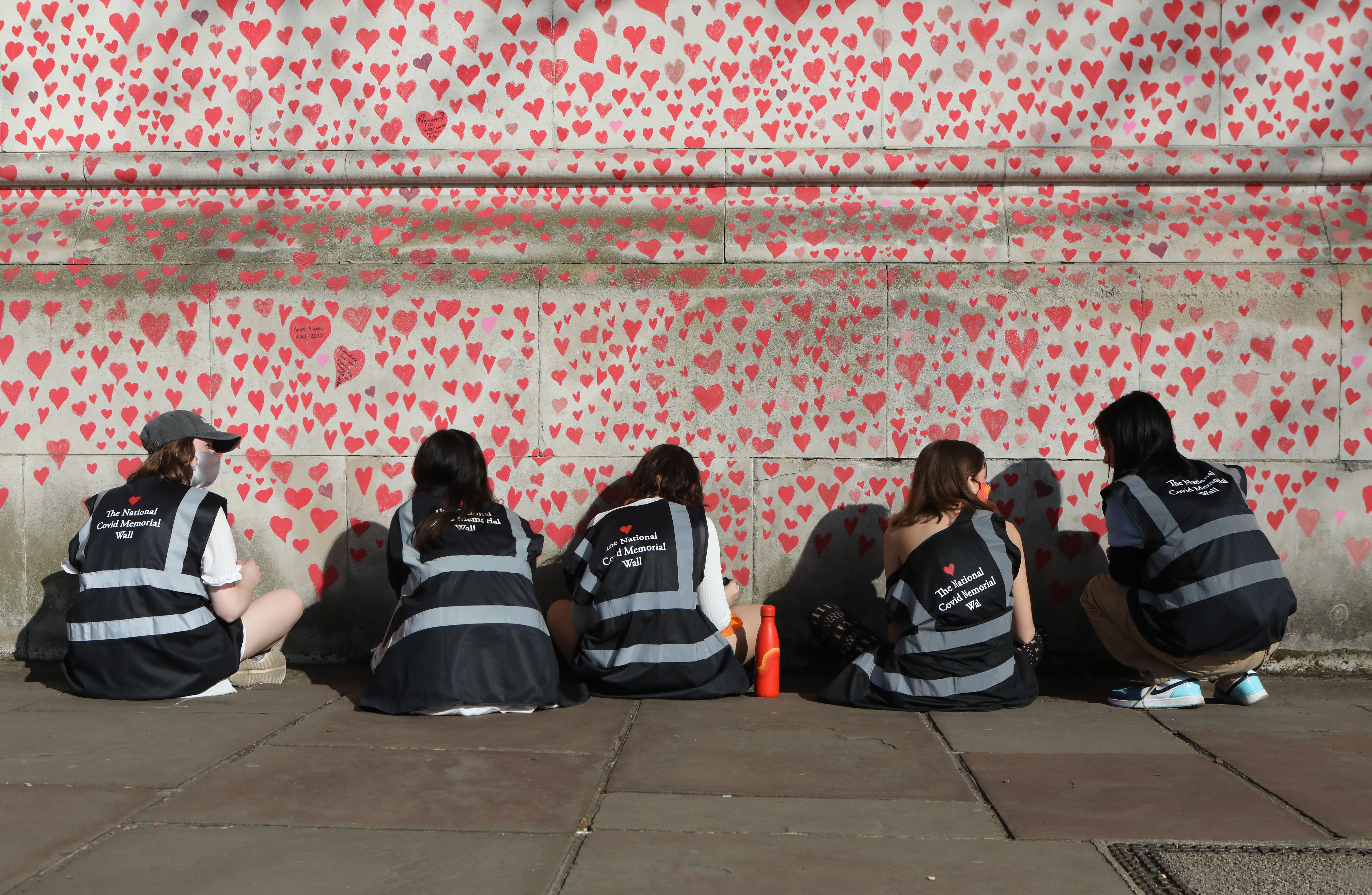 <p>People draw hearts on the National Covid Memorial Wall on the Embankment, central London, which is being painted in memory of the more than 145,000 people who have died in the UK from coronavirus. Picture date: Tuesday March 30, 2021.</p>
