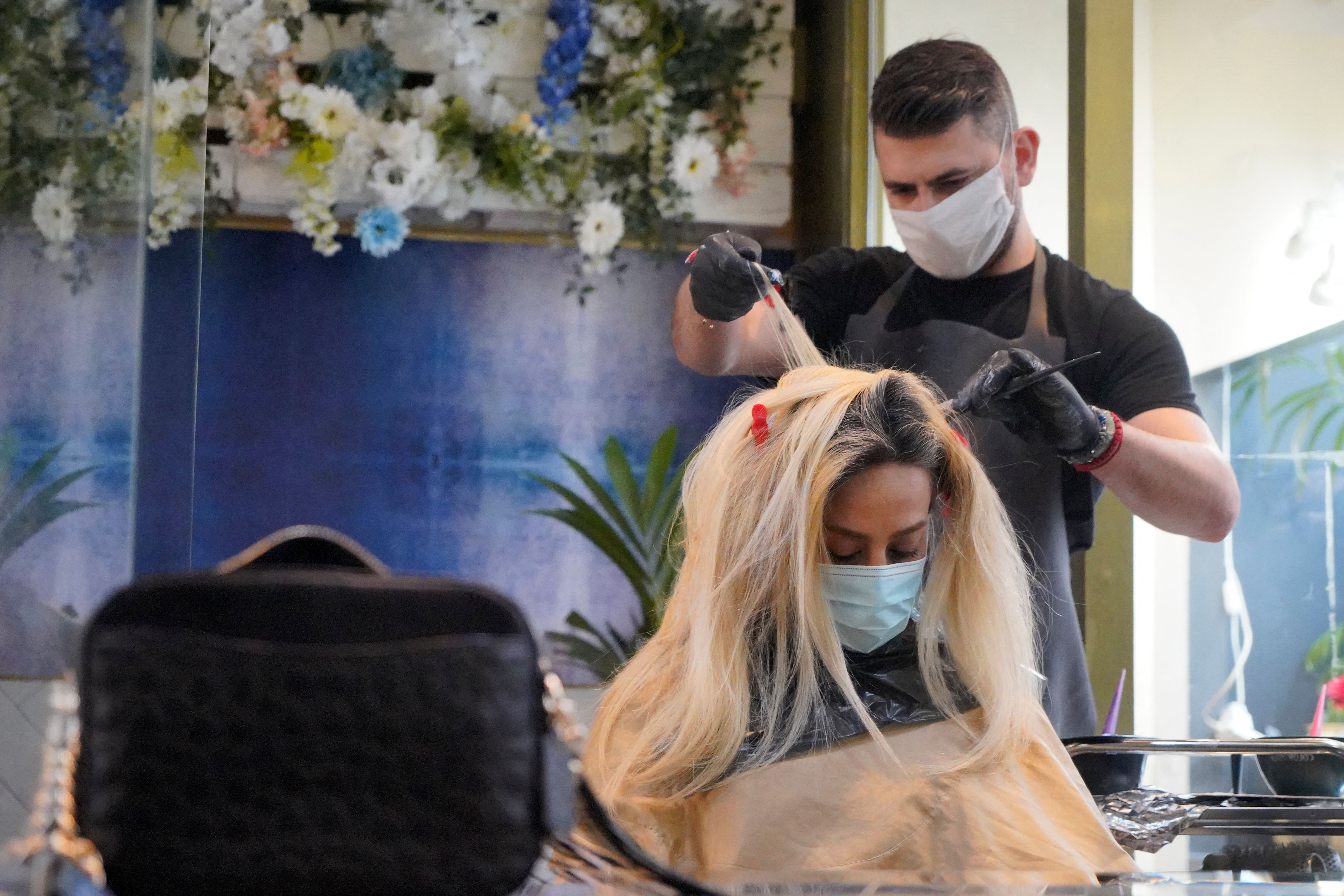 <p>Hairdressers work on a client at Gusto Hair salon in central London as it reopens following the easing of coronavirus restrictions after England's third national lockdown on April 12, 2021 (Photo by Niklas HALLE'N / AFP) (Photo by NIKLAS HALLE'N/AFP via Getty Images)</p>