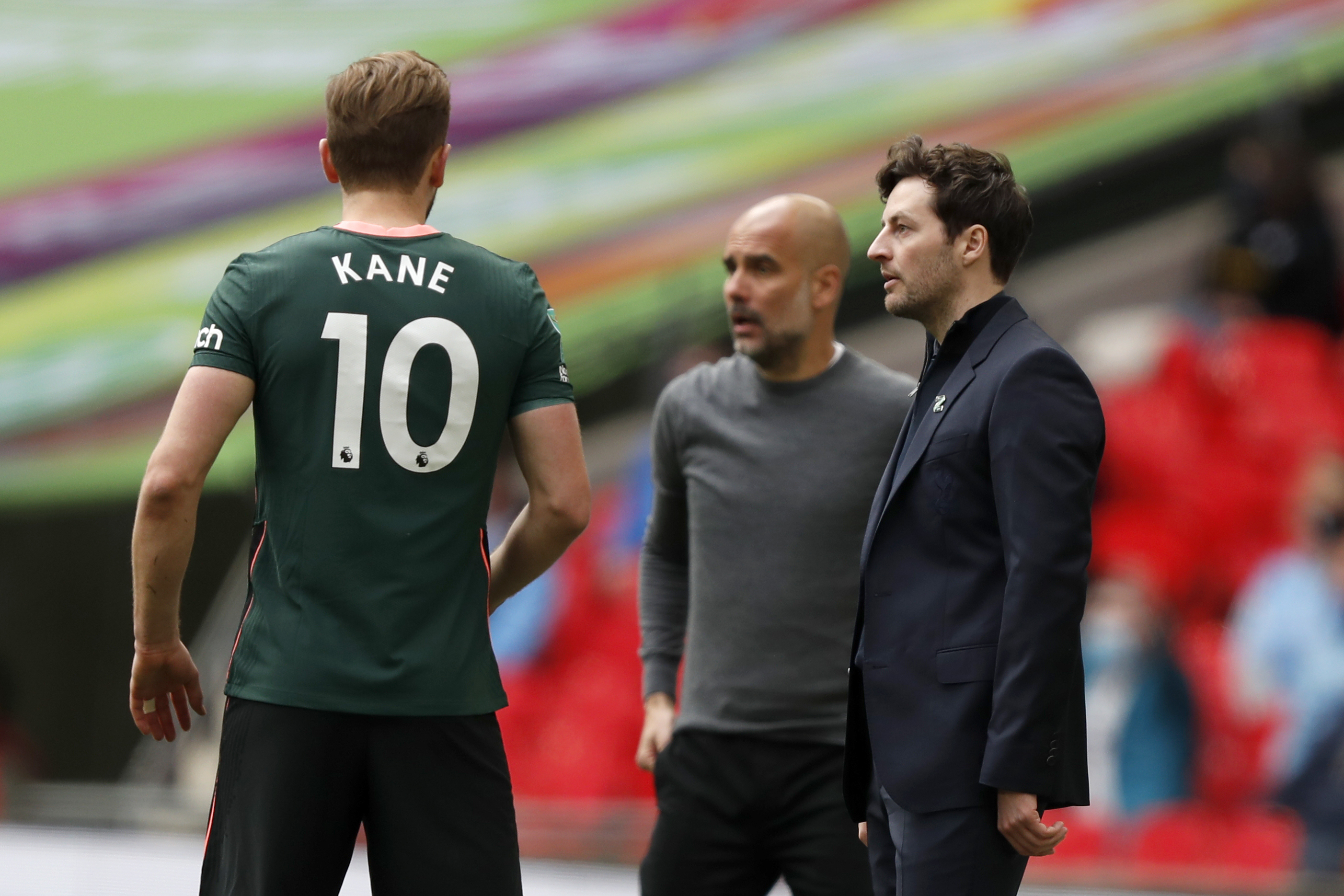 <p>Tottenham's interim head coach Ryan Mason talks to Tottenham's Harry Kane, with Manchester City's head coach Pep Guardiola in the background, during the English League Cup final soccer match between Manchester City and Tottenham Hotspur at Wembley stadium in London, Sunday, April 25, 2021. (AP Photo/Alastair Grant)</p>