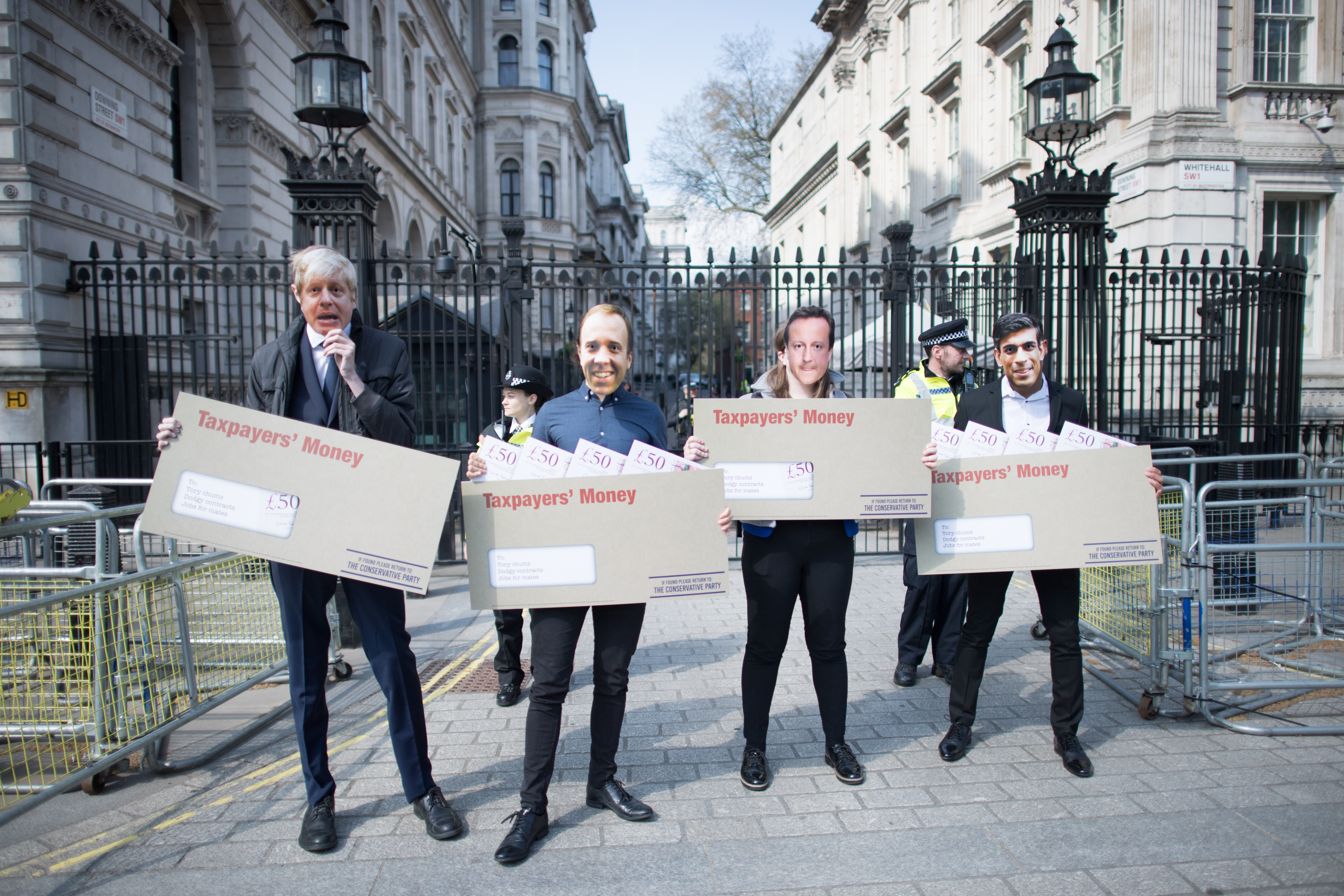 "<p>Labour activists wearing face masks, depicting Prime Minister Boris Johnson, Chancellor Rishi Sunak, Health Secretary Matt Hancock and former prime minister David Cameron, carry oversized envelopes addressed to ""Tory chums, Dodgy contracts, Jobs for mates"" as the Labour party highlight Tory sleaze and cronyism outside Downing Street, London. Picture date: Wednesday April 21, 2021.</p>"