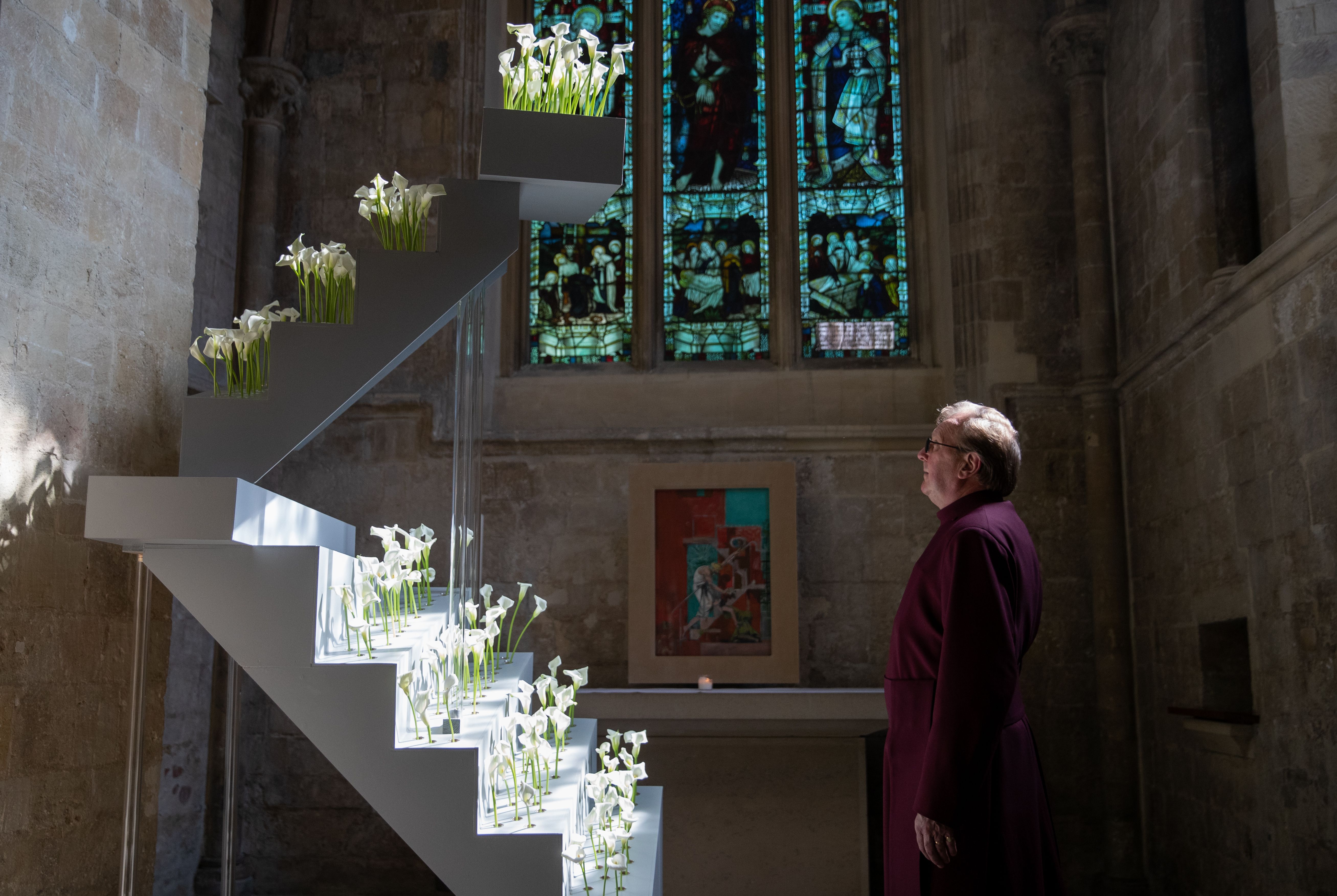 <p>Head verger Howard Waddell looks at a floral installation made with calla-lilies in the Mary Magdalene Chapel at Chichester Cathedral. Picture date: Sunday April 4, 2021. The structure, mirroring the staircase in Graham Sutherland???s painting 'Noli me Tangere' which is also located in the Chapel, was created to mark the end of Holy Week and the installation will be an opportunity to help people remember those impacted by the coronavirus pandemic.</p>