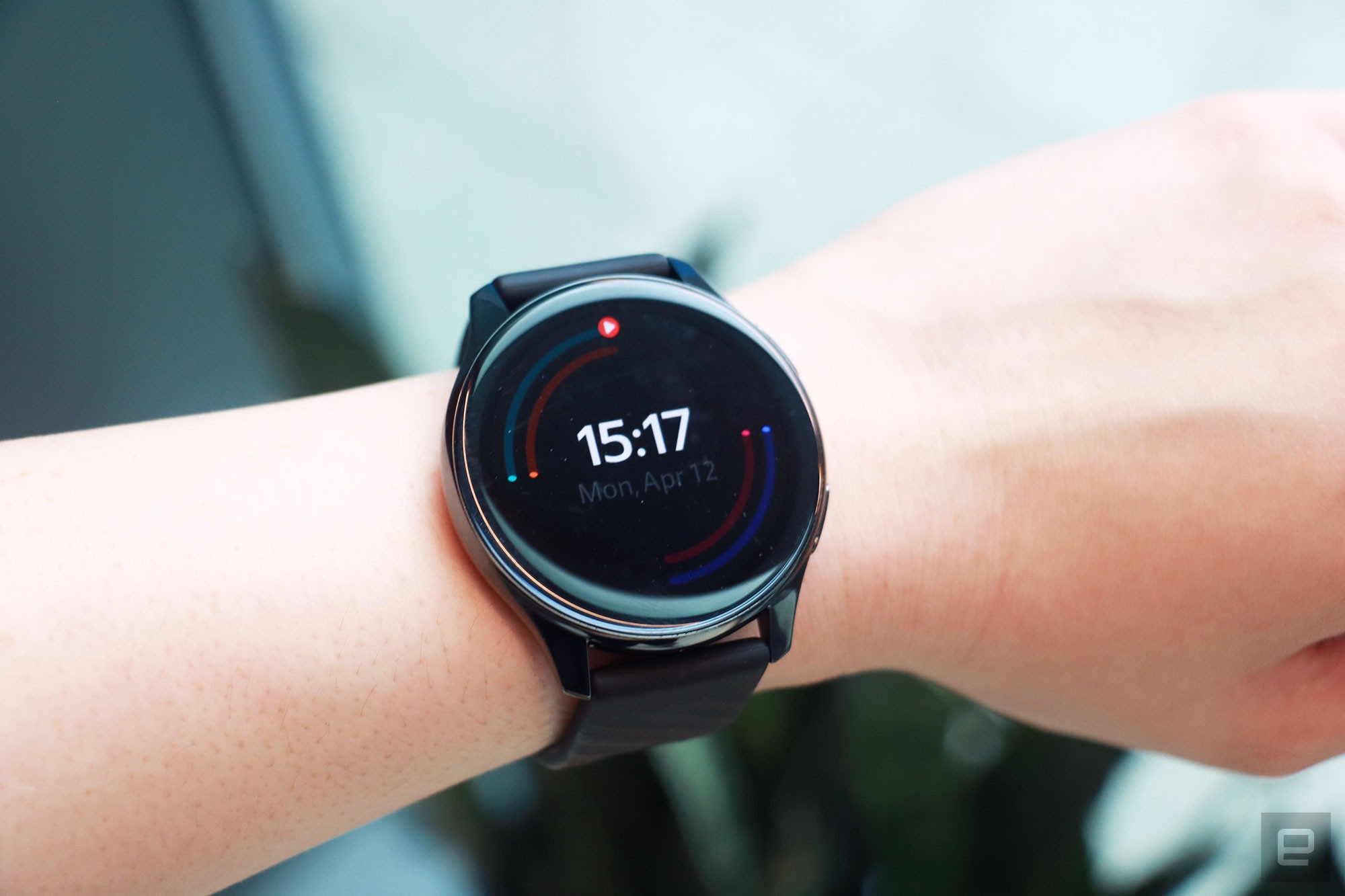 <p>OnePlus Watch review photos. OnePlus Watch on a wrist with display showing the time and outlines of rings in different colors around the face.</p>