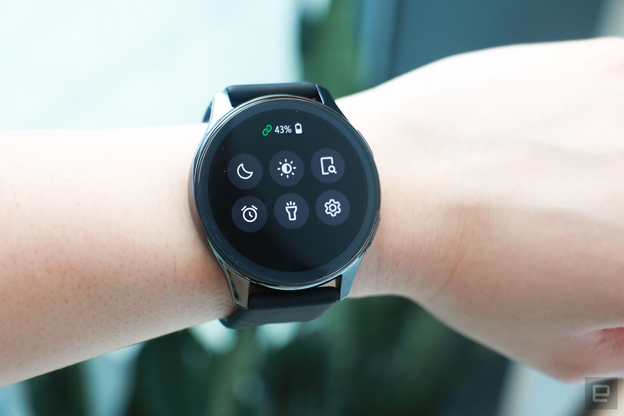 <p>OnePlus Watch review photos. OnePlus Watch on a wrist showing quick settings panel with icons for do not disturb, find my phone, alarms, flashlight, settings and brightness, as well as a battery indicator showing 43 percent.</p>