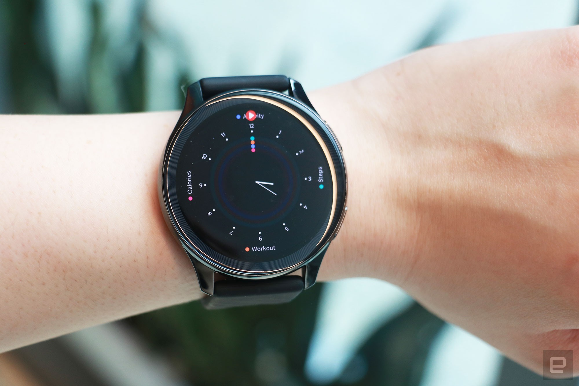 <p>OnePlus Watch review photos. OnePlus Watch on a wrist showing a faux analog watch face with markers for progress on Calories, Steps and Workout.</p>