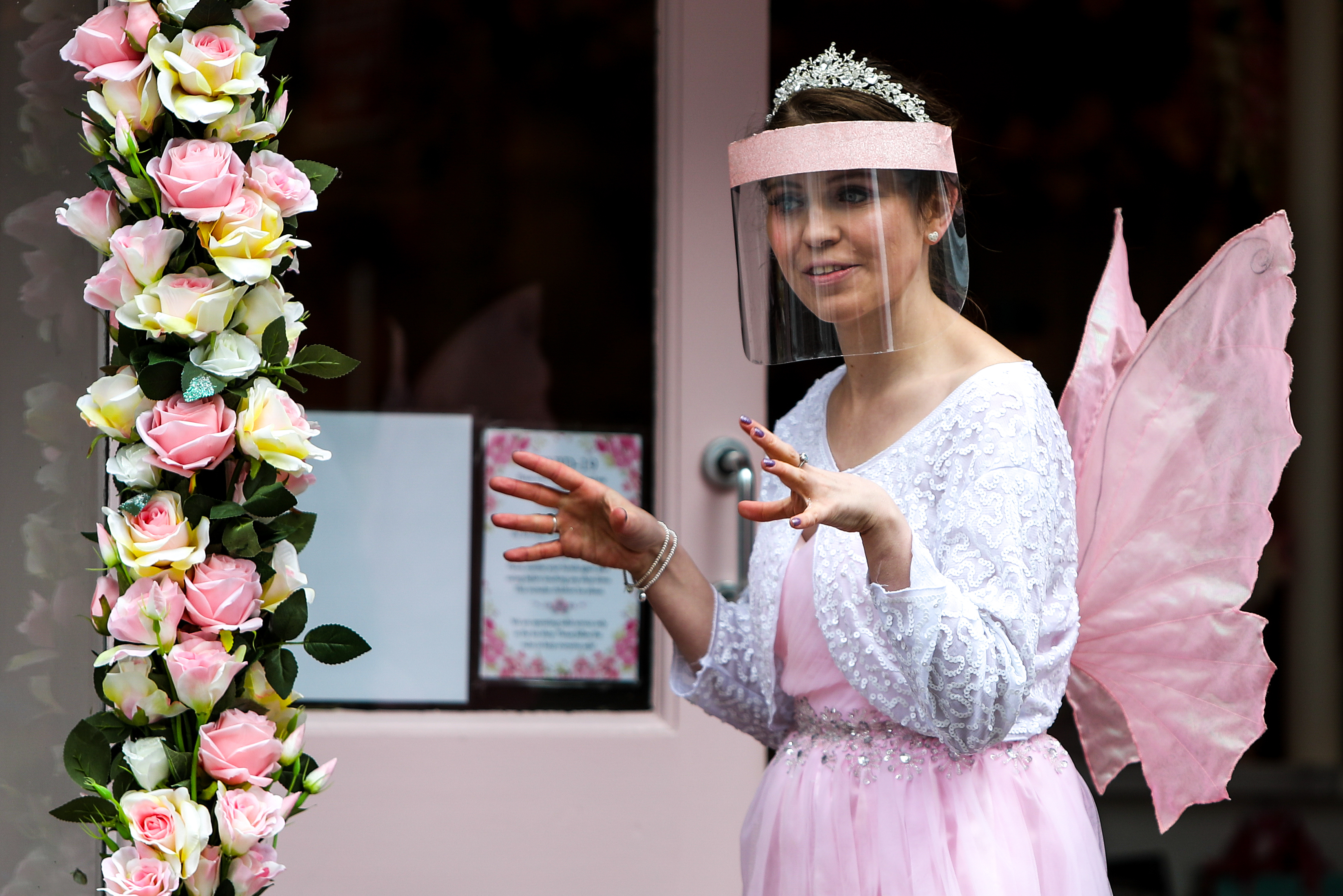 <p>A waitress dressed as a fairy serves a customer outside the Petite Fairytale Boutique in Worthing town centre, Sussex, as England takes another step back towards normality with the further easing of lockdown restrictions. Picture date: Monday April 12, 2021.</p>