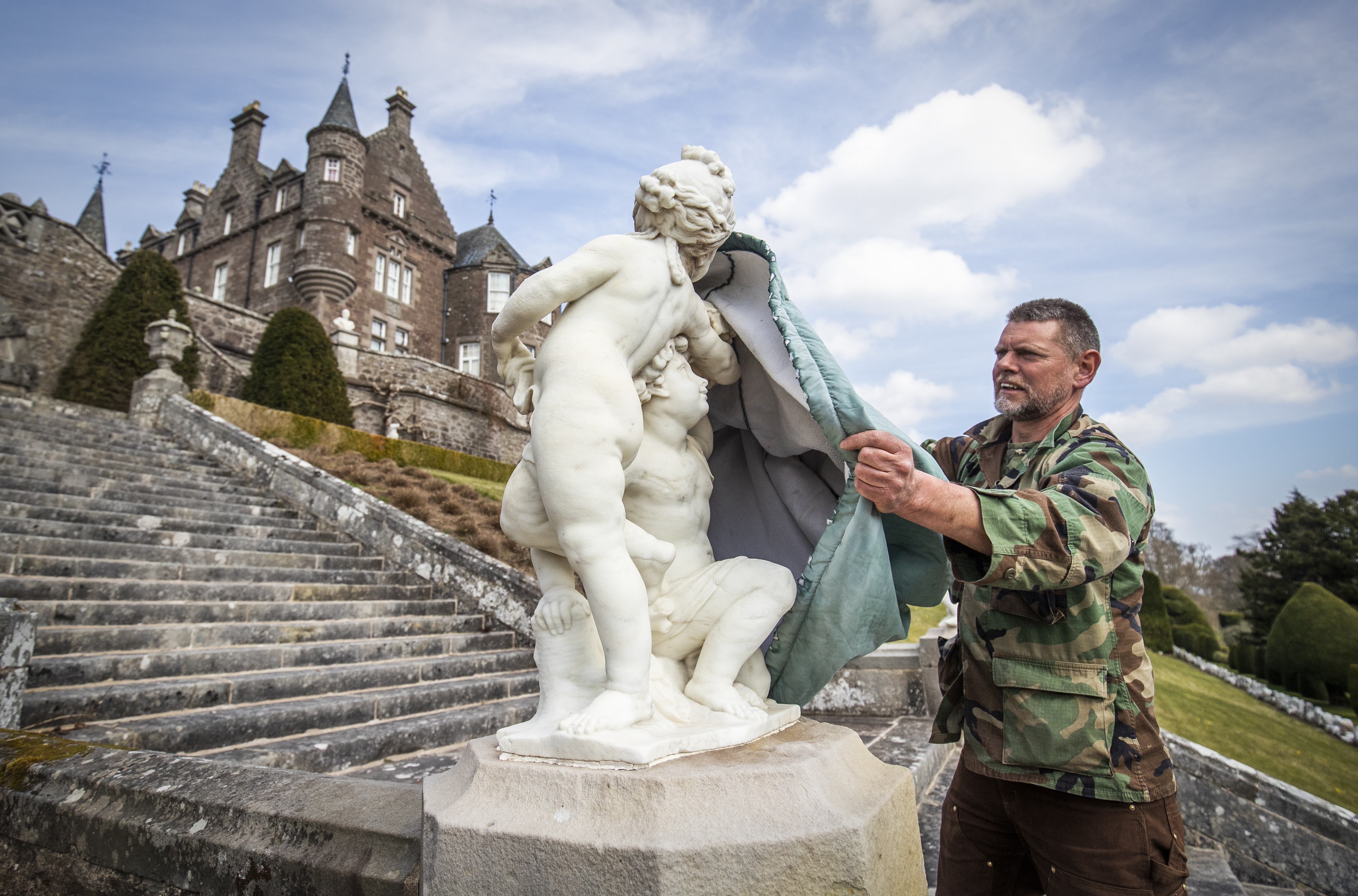 <p>Gardener Andy Ayre unwraps the collection of marble statues from their winter coverings at Drummond Castle Gardens in Perthshire, in preparation for the Gardens reopening to the public on Saturday May 1, for the first time since October 2019. The statues are carefully wrapped each autumn to protect them from the winter frosts and unwrapped and sprayed each spring. Picture date: Monday April 19, 2021.</p>