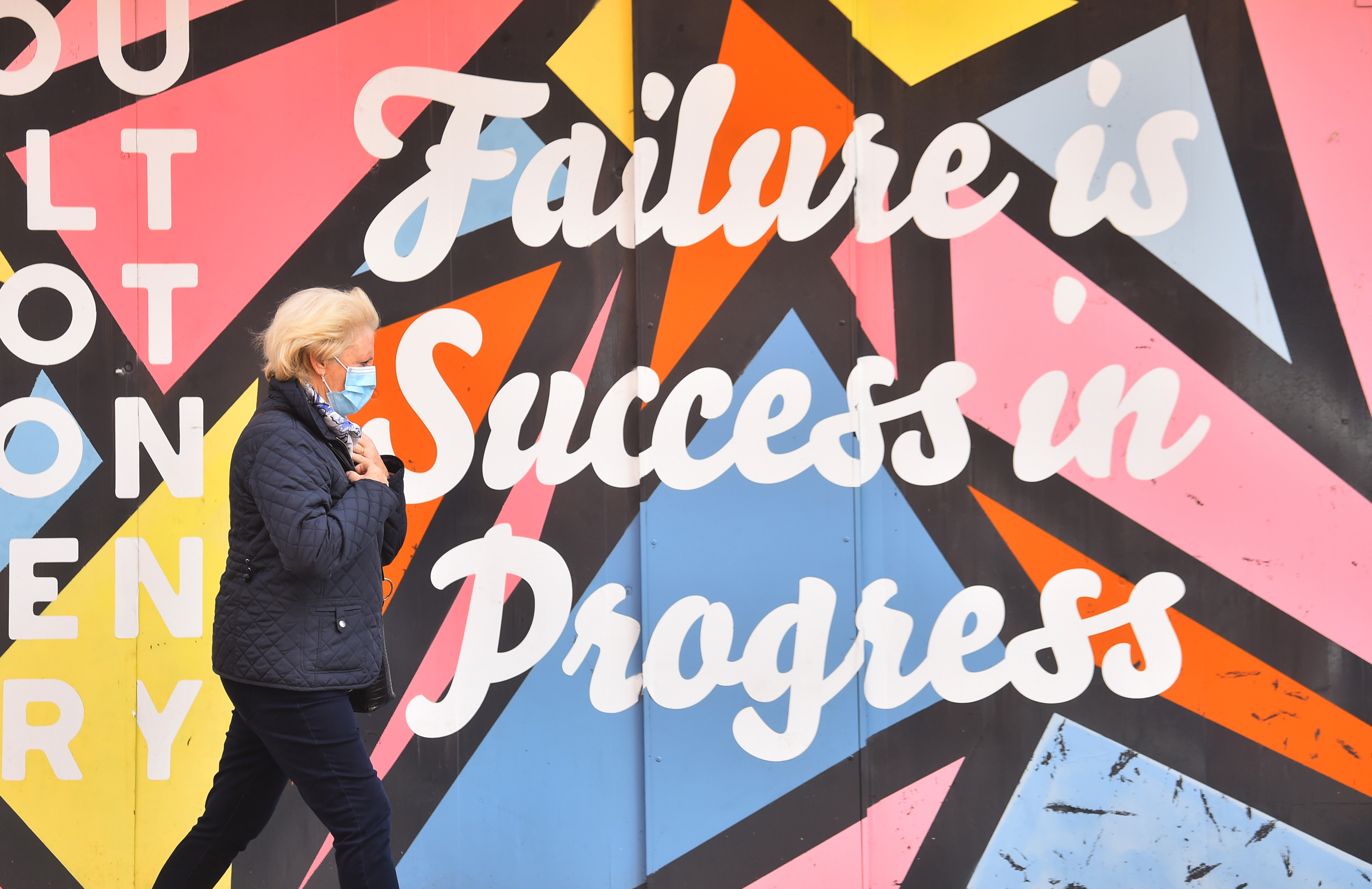 <p>STOKE-ON-TRENT, ENGLAND - APRIL 08: A lady wearing a mask walks past artwork saying 'Failure is success in progress' on April 08, 2021 in Stoke-on-Trent,England . (Photo by Nathan Stirk/Getty Images)</p>