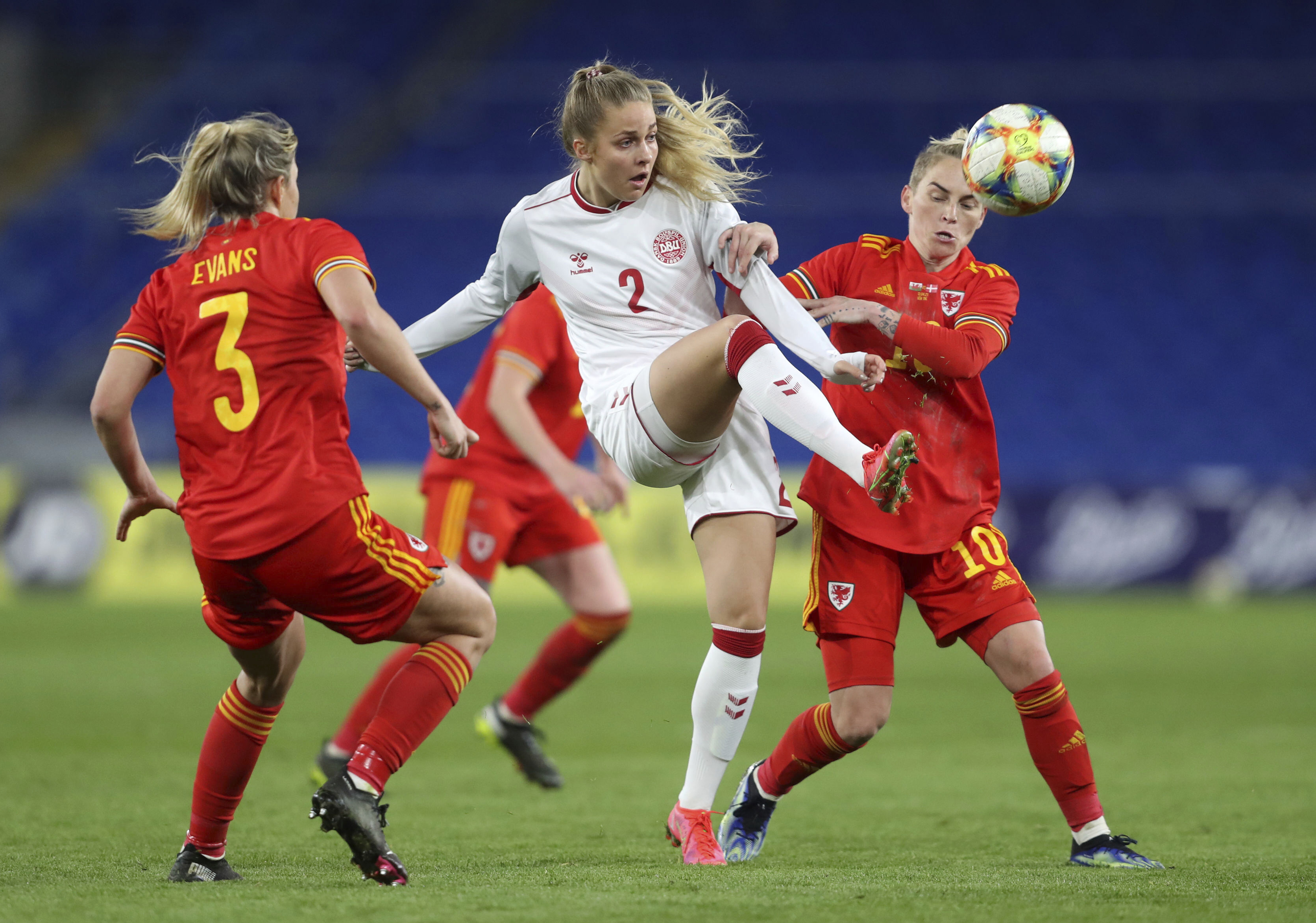 <p>Denmark's Olivia Holt, centre, and Wales' Jess Fishlock, right, during their women's international friendly soccer match at Cardiff City Stadium, Cardiff, Wales, Tuesday April 13, 2021. (David Davies/PA via AP)</p>