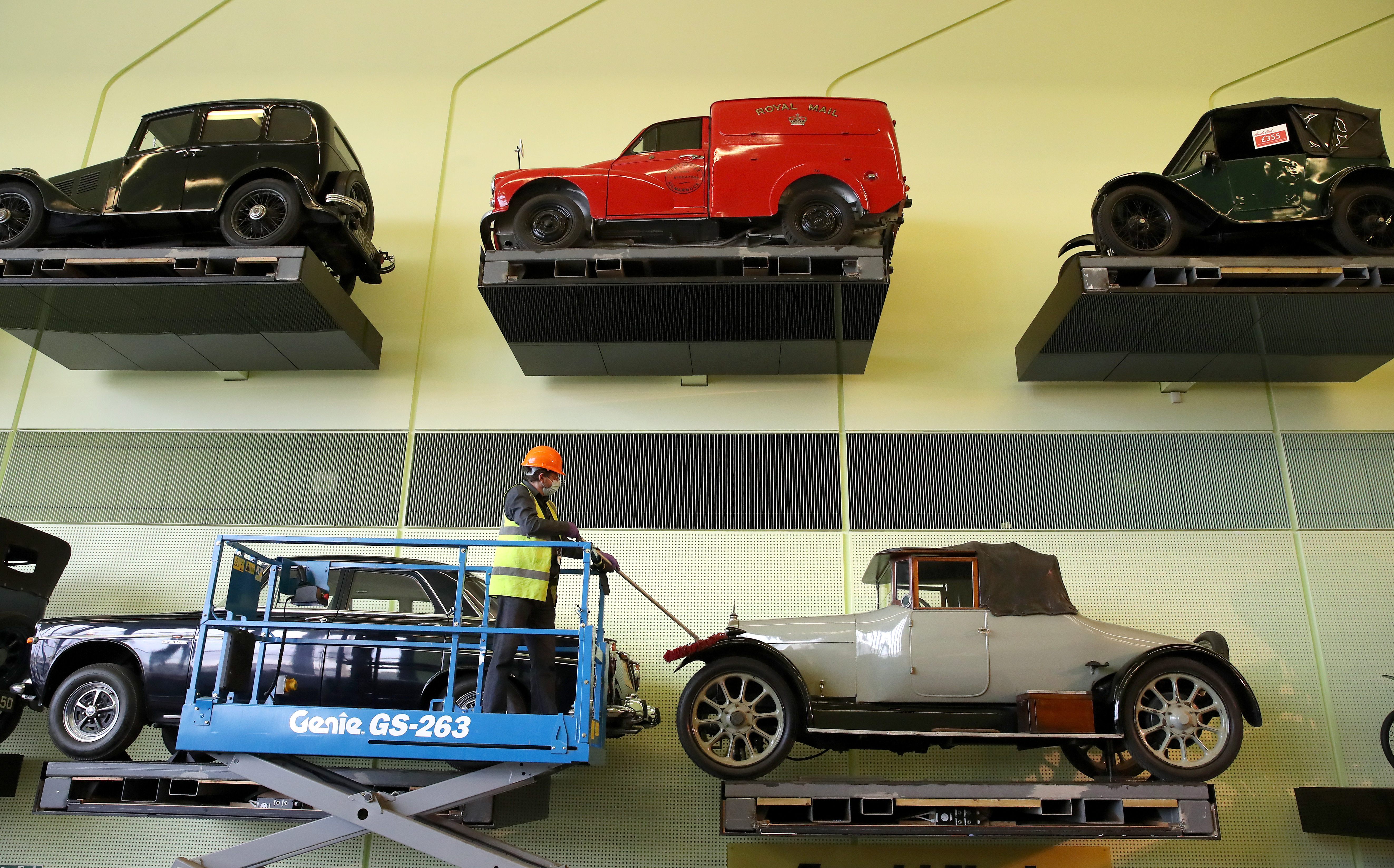 <p>Jacek Wiklo conservator at the Riverside Museum in Glasgow dusts the cars on the car wall ahead of the museum re-opening on Monday as lockdown restrictions in Scotland have begun to gradually ease. Picture date: Tuesday April 20, 2021.</p>