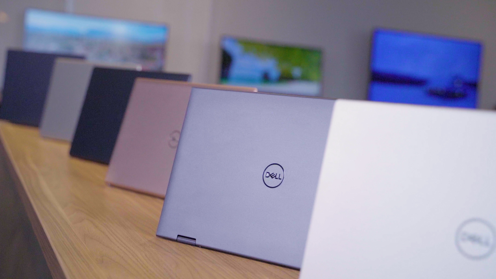 <p>Dell Inspiron redesign 2021. A closeup of the lids of six Dell Inspiron laptops laid out on a wooden table in gray, silver and copper colors.</p>