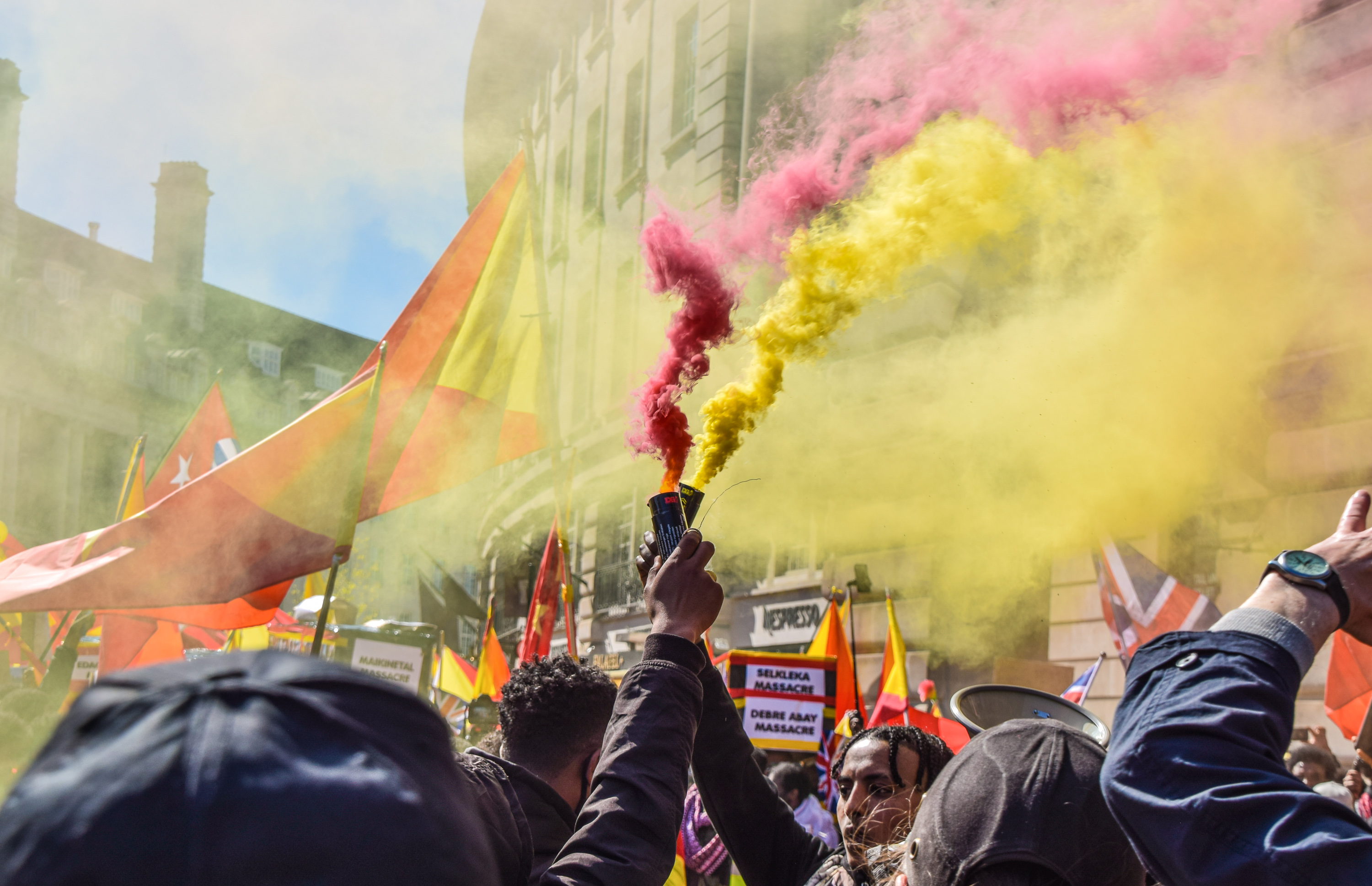 """<p>LONDON, UNITED KINGDOM - 2021/04/25: Protesters hold smoke flares during the demonstration. Thousands of people marched through Central London in protest of what the demonstrators call Ethiopia's and Eritrea's """"genocidal war"""" on the region of Tigray. (Photo by Vuk Valcic/SOPA Images/LightRocket via Getty Images)</p>"""