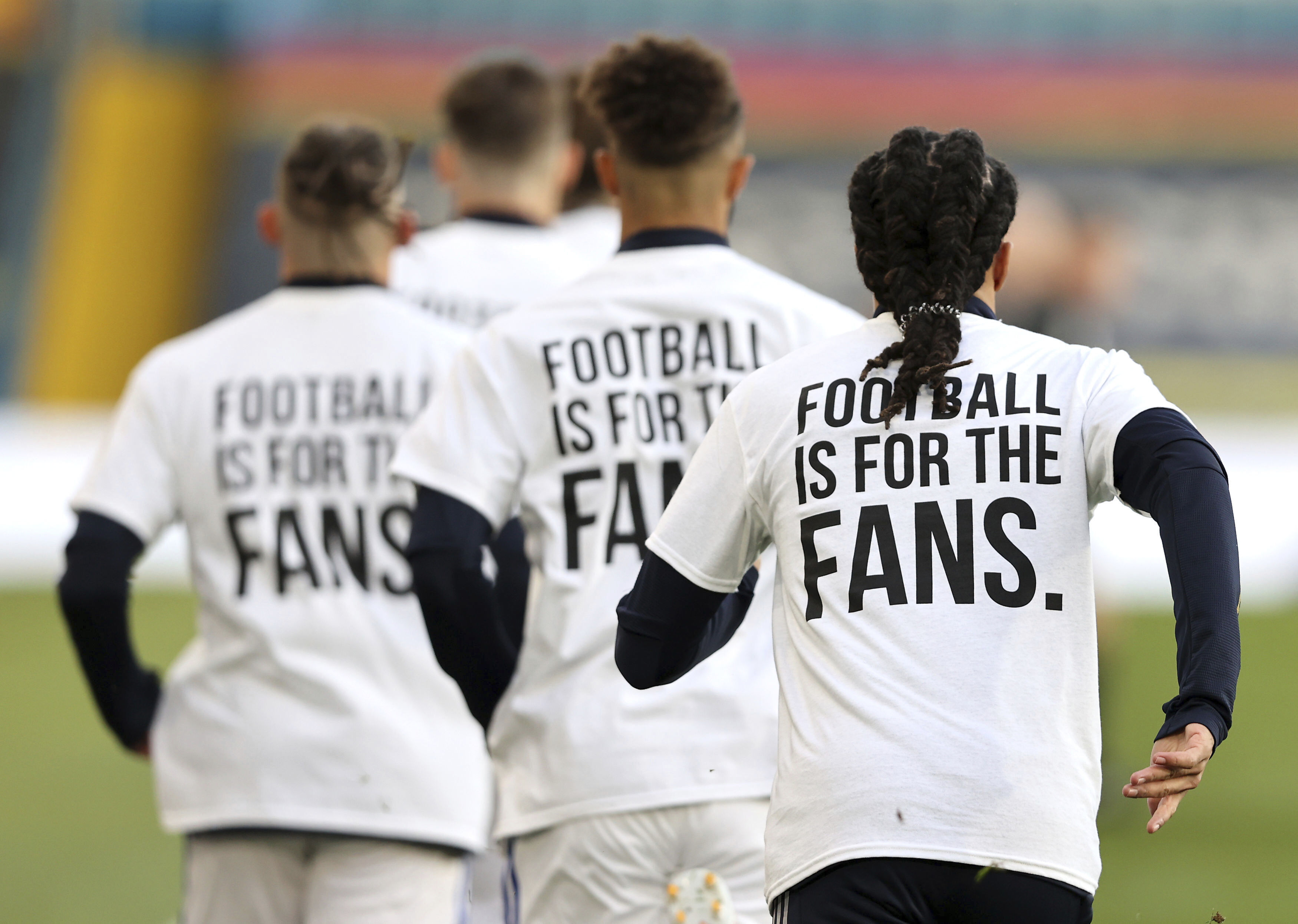<p>Leeds United players wear t-shirts with the logo 'Football Is For The Fans' as they warm-up ahead of ahead of the English Premier League soccer match between Leeds United and Liverpool at the Elland Road stadium in Leeds, England, Monday, April 19, 2021. (Clive Brunskill/Pool via AP)</p>