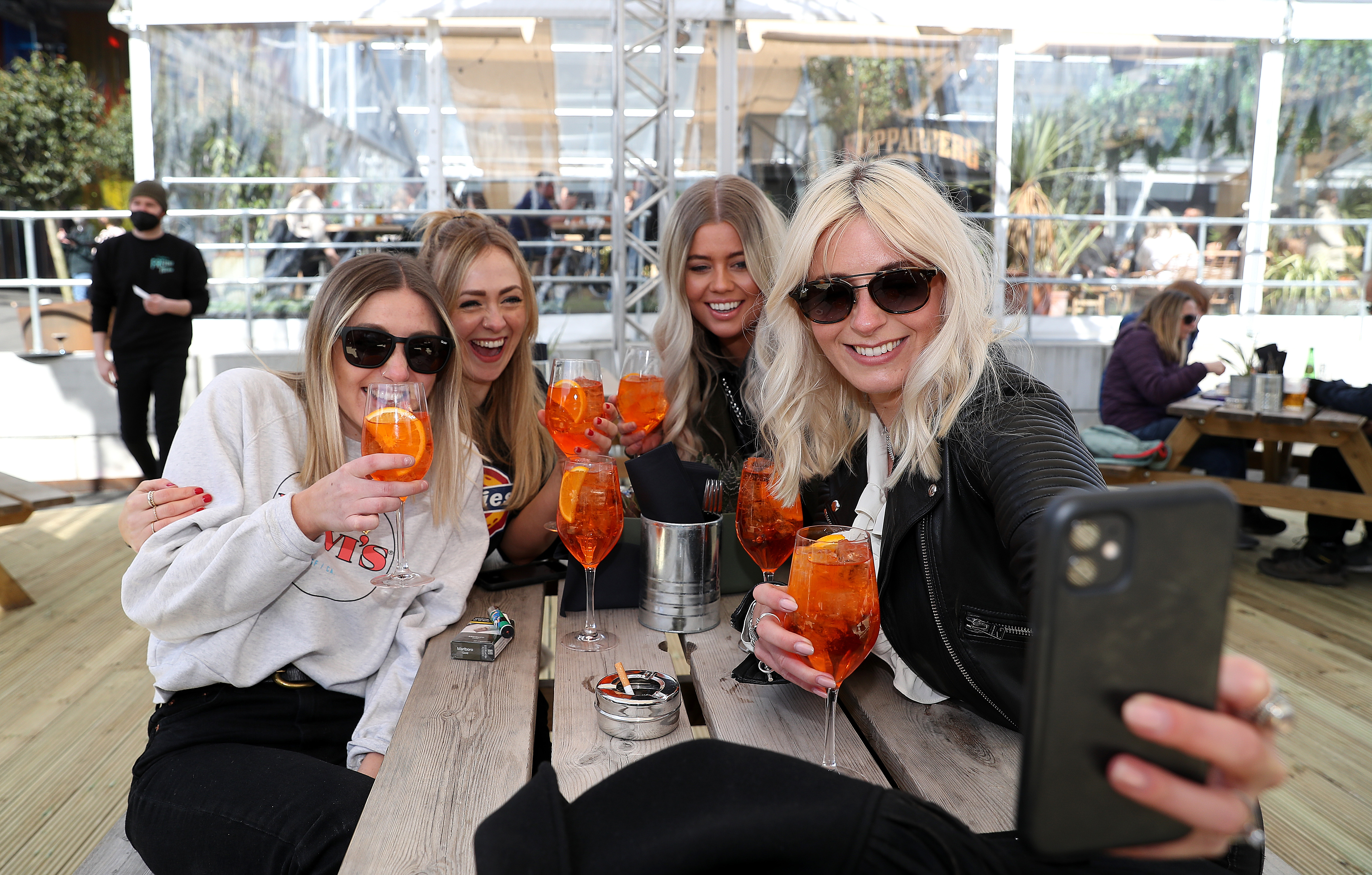 <p>(Left to right) Sara Barnes, Katie Davies, Amber Harrison and Georgia Noon take a selfie as they enjoy a drink at the Escape to Freight Island bar in Depot Island, Manchester, as England takes another step back towards normality with the further easing of lockdown restrictions. Picture date: Monday April 12, 2021.</p>