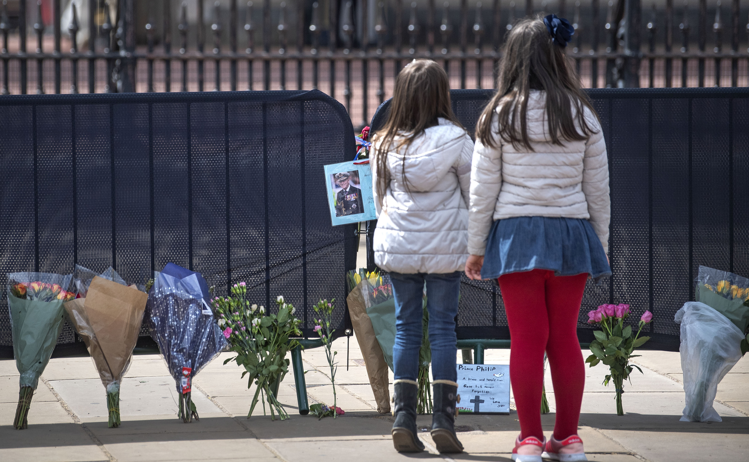 <p>Two girls look at flowers and messages left by members of the public outside Buckingham Palace, London, following the death of the Duke of Edinburgh at the age of 99 on Friday. Picture date: Tuesday April 13, 2021.</p>