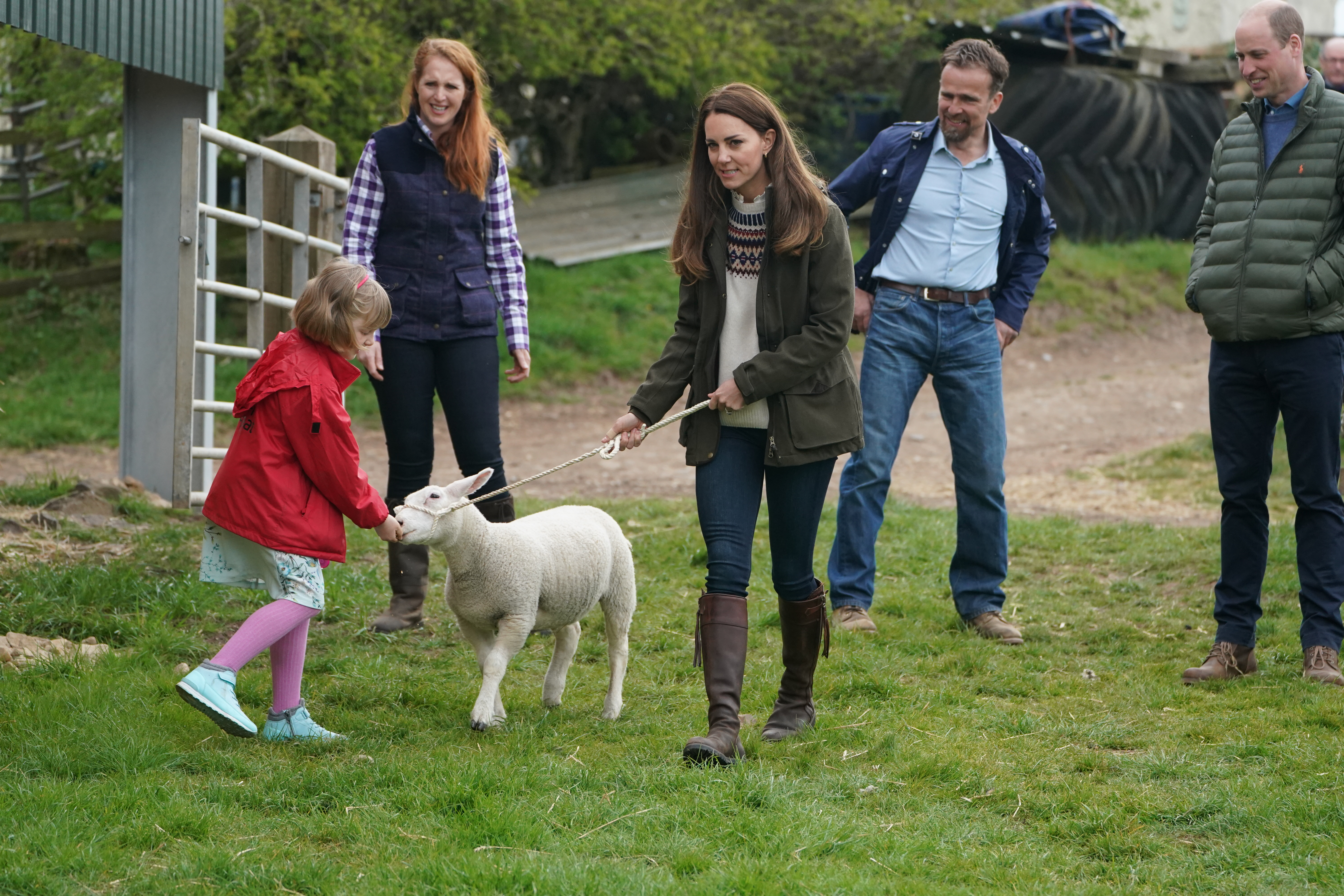 <p>The Duchess of Cambridge and farmer's daughter Clover Chapman, 9, walk a lamb together, watched by her parents and the Duke of Cambridge, during a royal visit to Manor Farm in Little Stainton, Durham. Picture date: Tuesday April 27, 2021.</p>