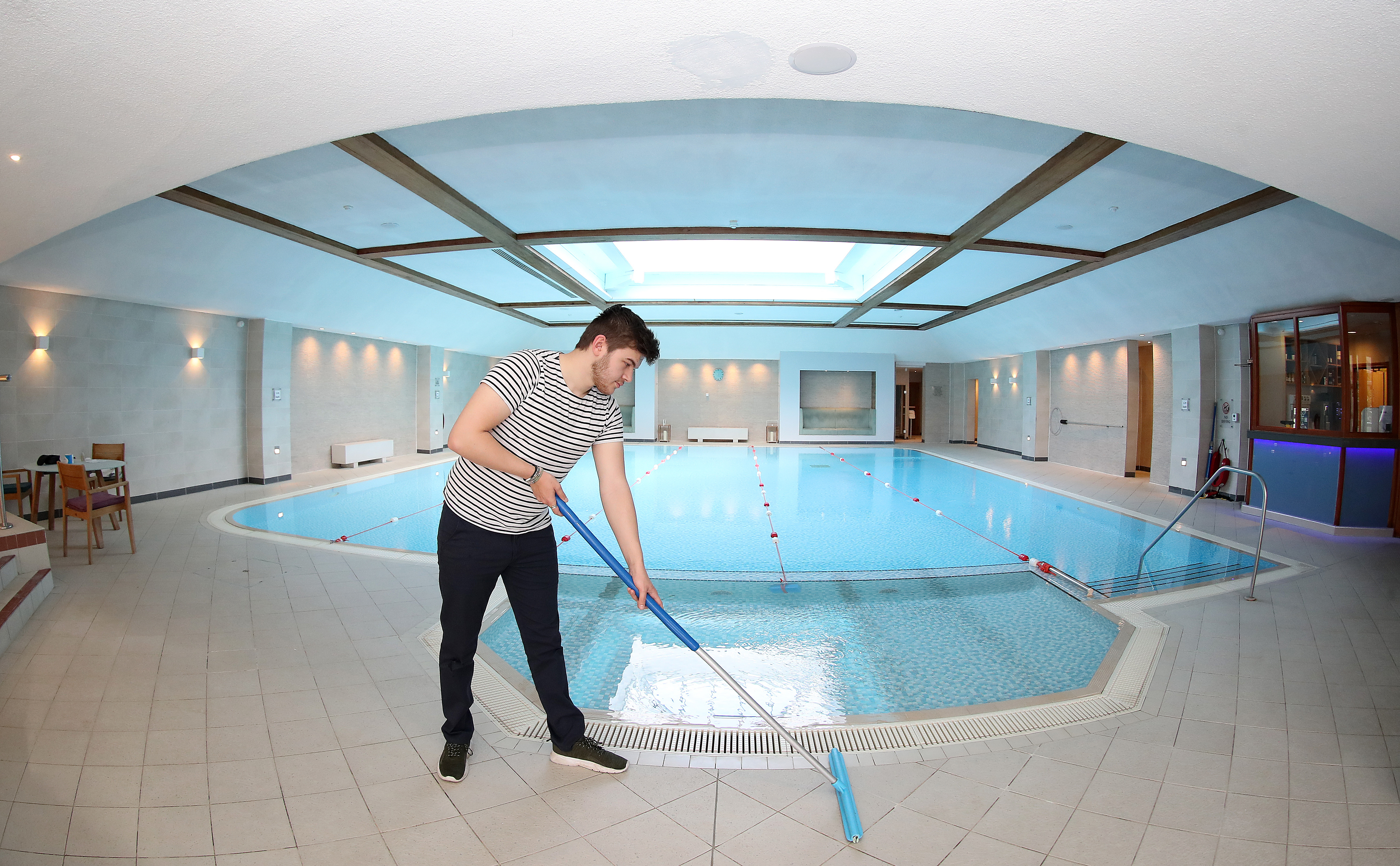 <p>Spa assistant Kieran Wilson cleans the pool deck at Cottons Hotel and Spa in Knutsford, Cheshire, ahead of reopening on Monday 12 April, as the second stage of England's lockdown roadmap begins. Picture date: Saturday April 10, 2021.</p>