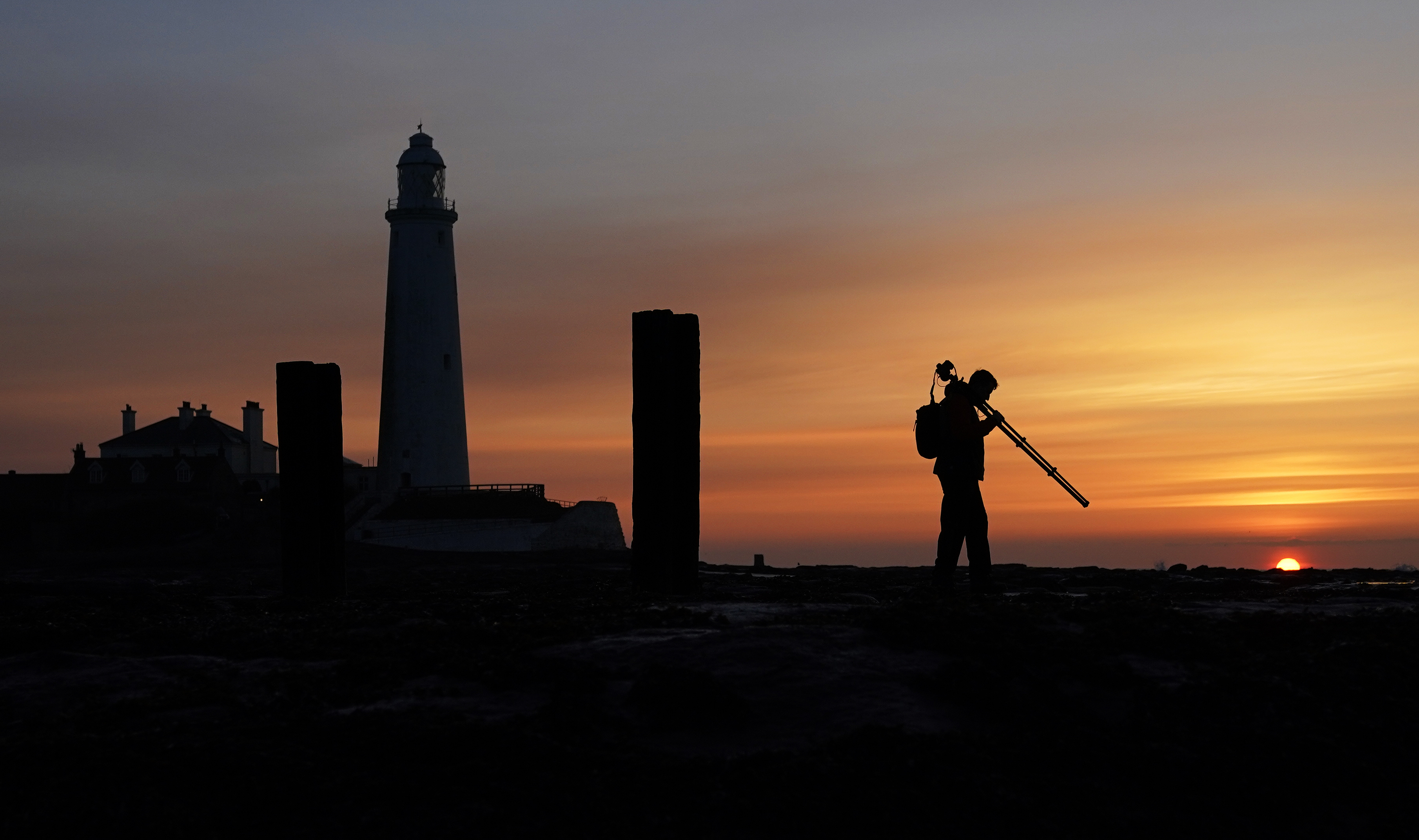 <p>A photographer lines up his shot before the sunrise at St Mary's Lighthouse in Whitley bay. Picture date: Monday April 26, 2021.</p>
