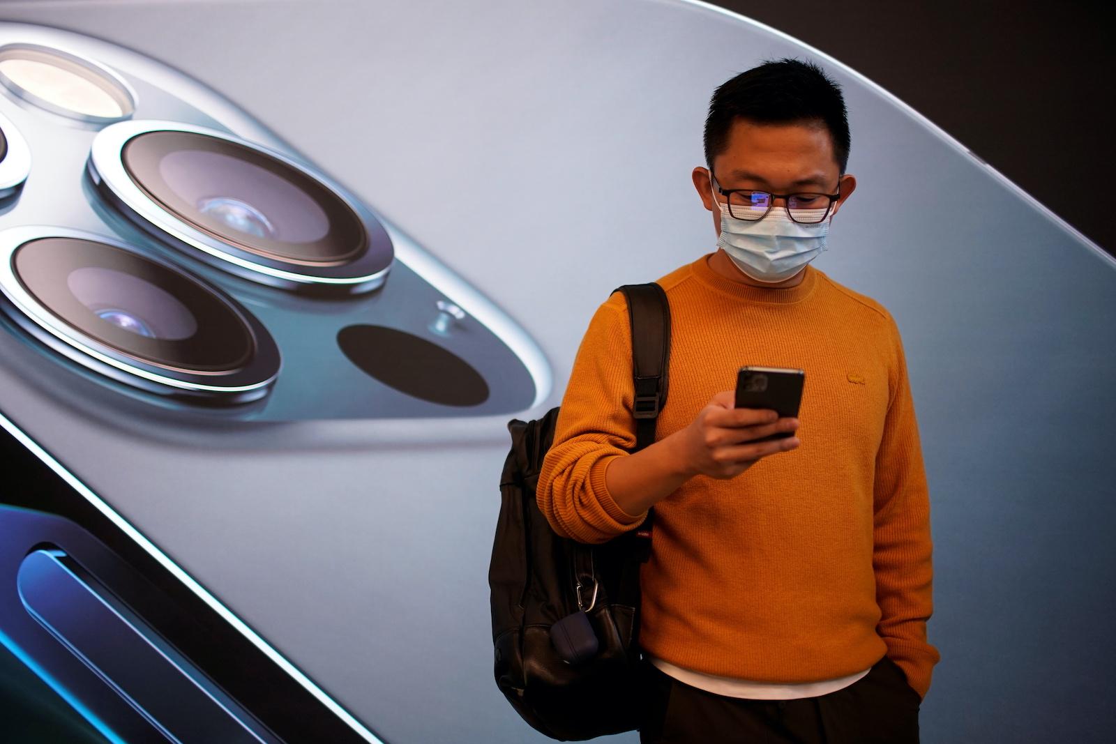 2020年10月23日,中國上海繼續爆發冠狀病毒病(COVID-19),一名男子戴著口罩在蘋果的5G新款iPhone 12上市之前。REUTERS / Aly Song-RC20OJ9HL7R3