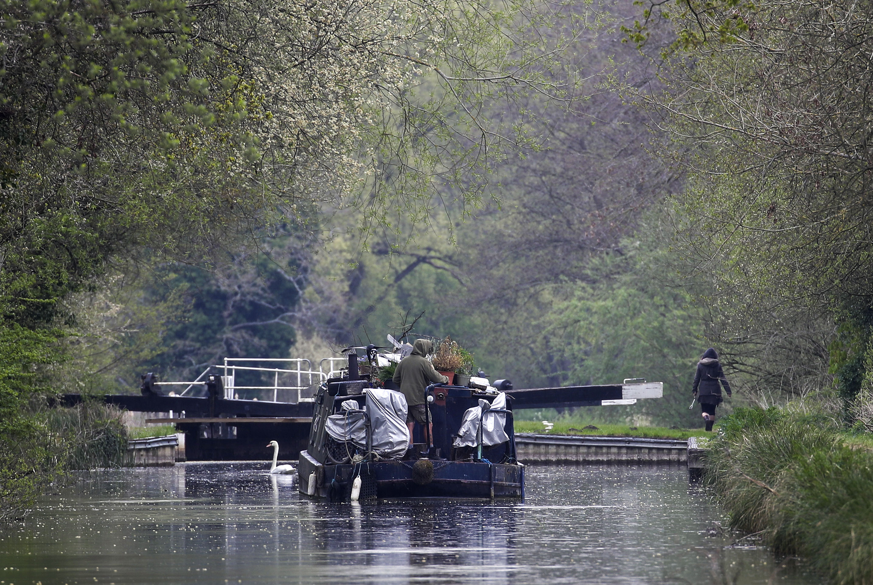 <p>A canal boat travels in the rain along the River Kennet near Theale, Berkshire. Picture date: Wednesday April 28, 2021.</p>