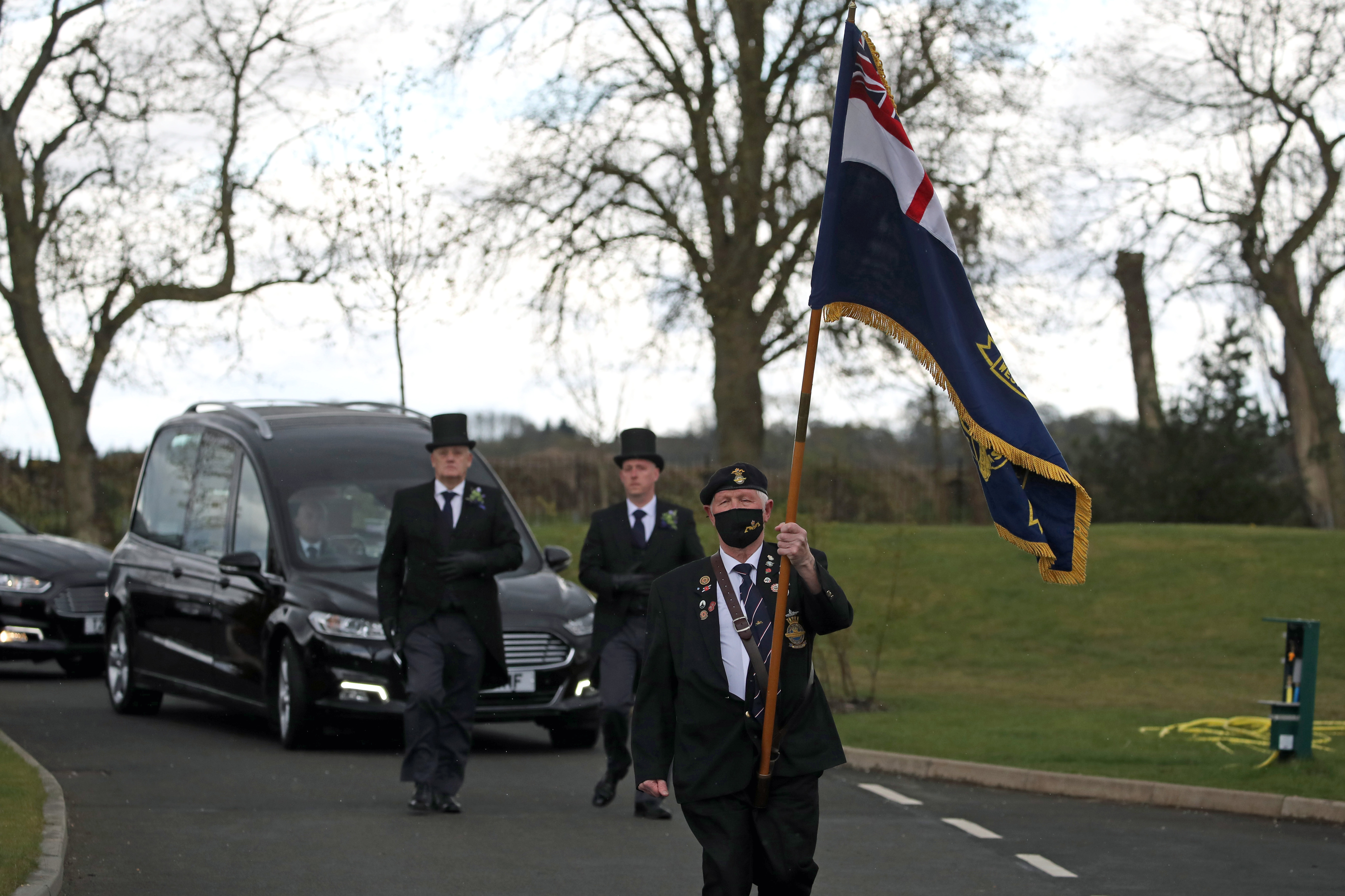 <p>A retired submariner walks in front of the cortege as it arrives at Stirling Crematorium, during the funeral of cyclist Anthony Parsons, whose body was found three years after he vanished. The former Navy petty officer, also known as Tony, went missing aged 63 in 2017 while on a long charity cycle from his home in Tillicoultry, Clackmannanshire, to Fort William. Picture date: Thursday April 29, 2021.</p>