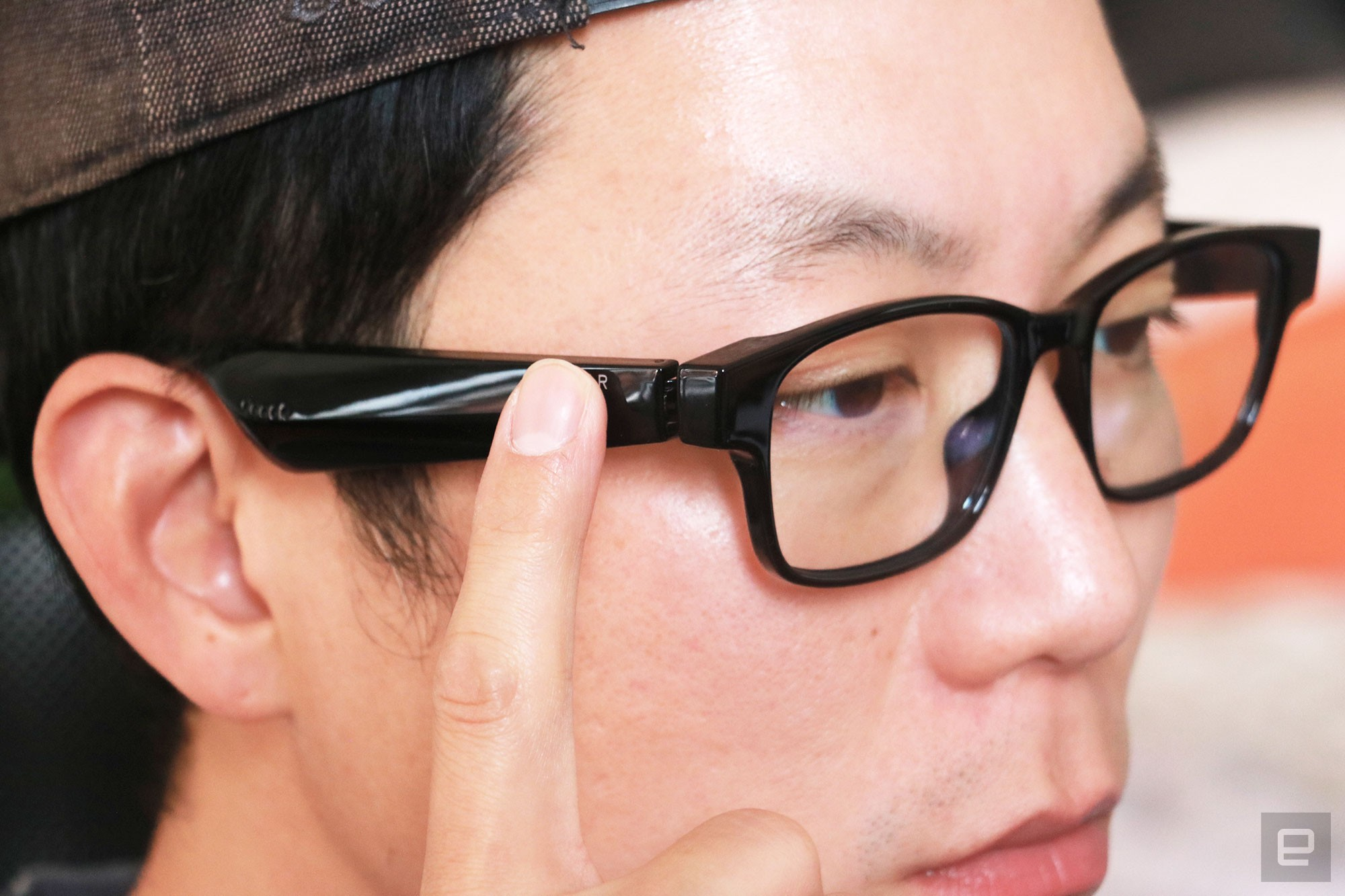 <p>Razer Anzu smart glasses review photo. Right side profile of a man wearing the Razer Anzu smart glasses with his right index finger up to the touch-sensitive arm.</p>