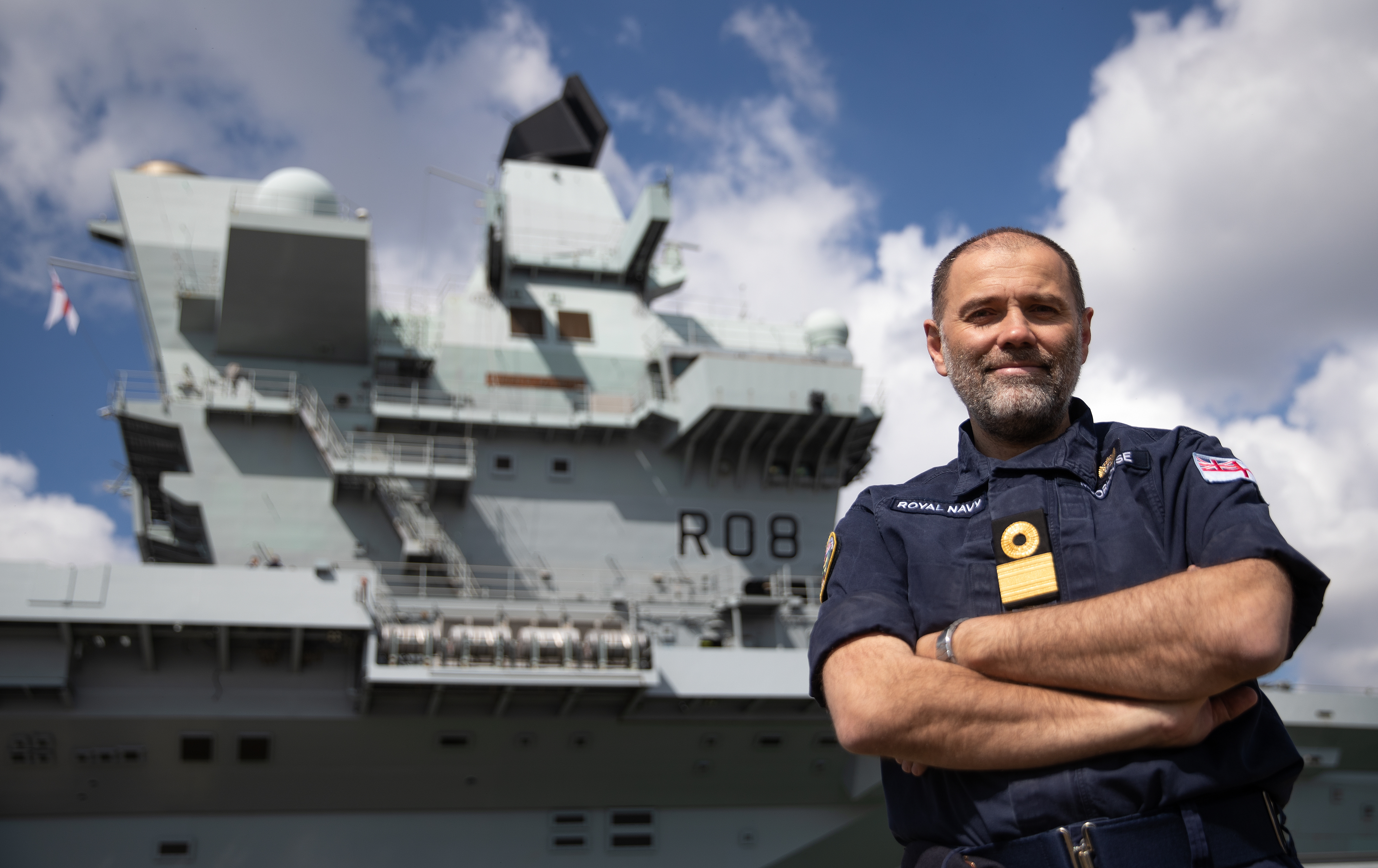 <p>Commodore Steve Moorhouse, Commander UK Carrier Strike Group, poses for a photograph in front of the Royal Navy aircraft carrier HMS Queen Elizabeth at Portsmouth Naval Base, Hampshire, as final preparations are made ahead its first operational deployment to the Indo-Pacific region. Picture date: Thursday April 29, 2021.</p>