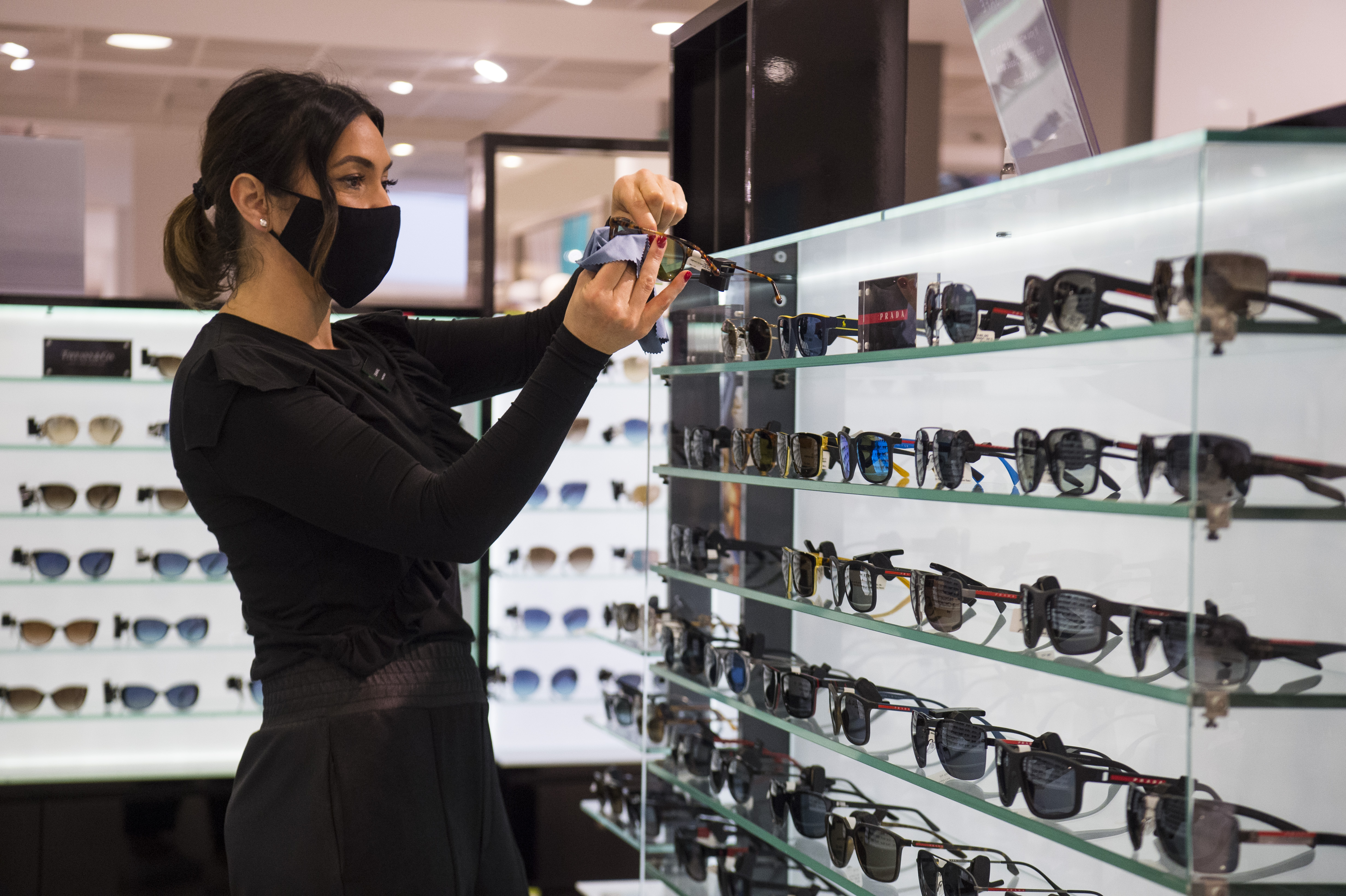 <p>A John Lewis partner polishes sunglasses at the Peter Jones store in Sloane Square, Chelsea, London, as they prepare for reopening on April 12 when further lockdown restrictions are eased in England. Picture date: Friday April 9, 2021.</p>