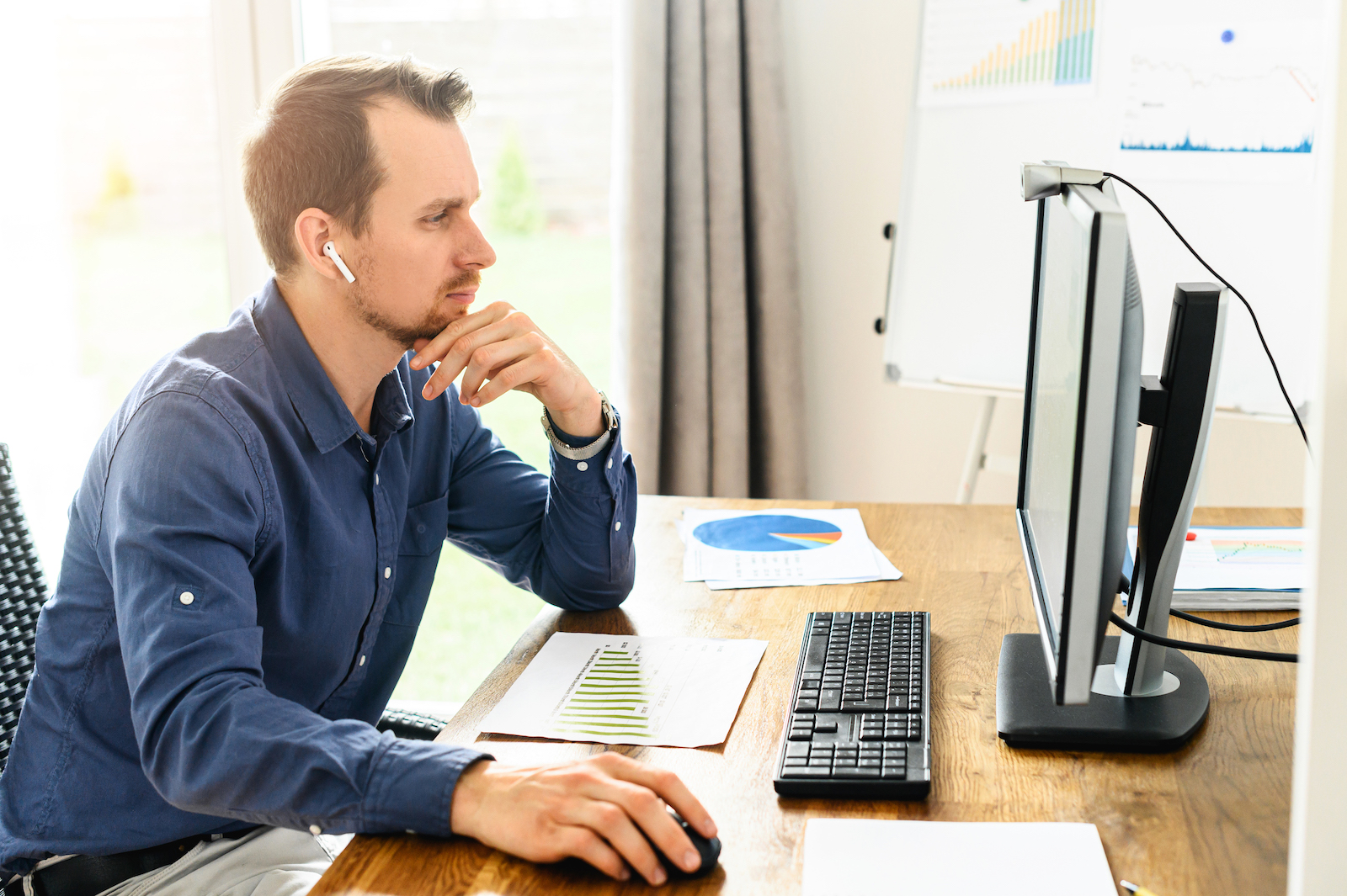 Work at office. A young man is using pc for office work, she sits at the table and concentrated looks to the screen, flip chart on background
