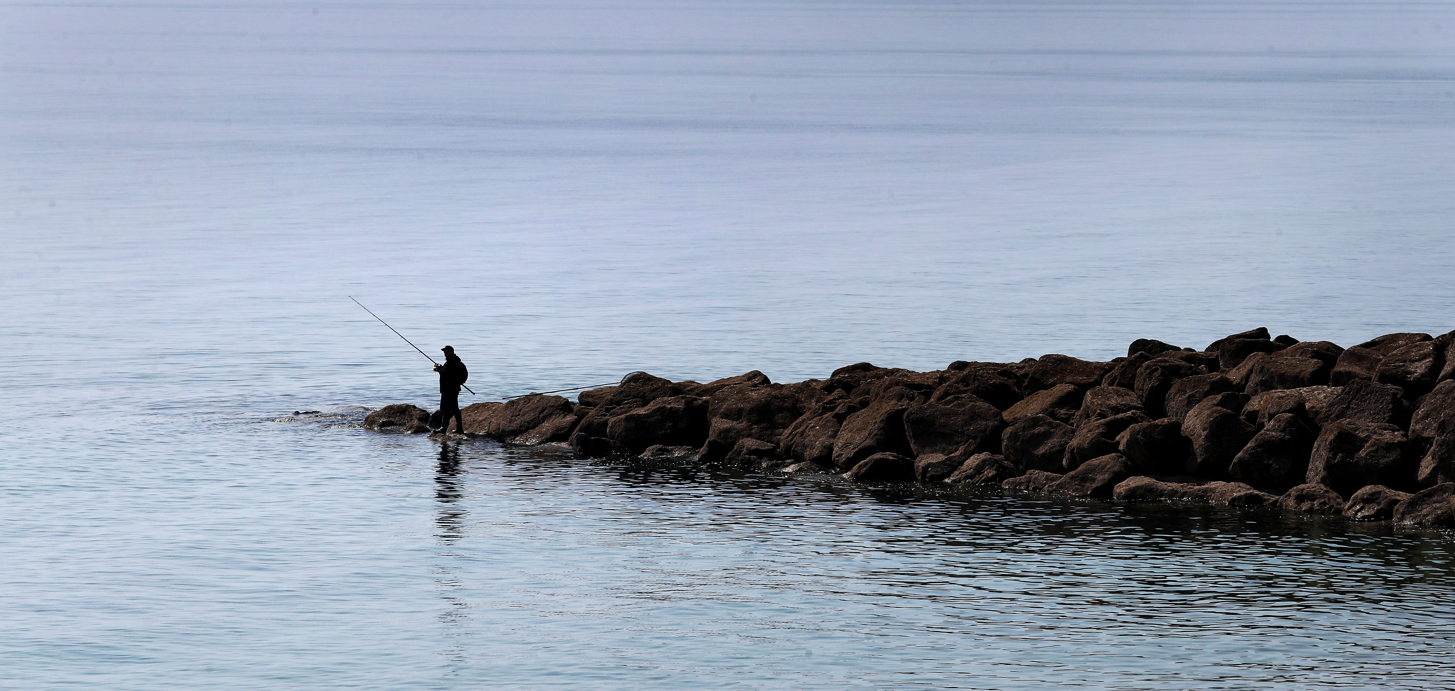 <p>A man enjoys fishing in the fine weather near Folkestone in Kent. Picture date: Monday April 19, 2021.</p>