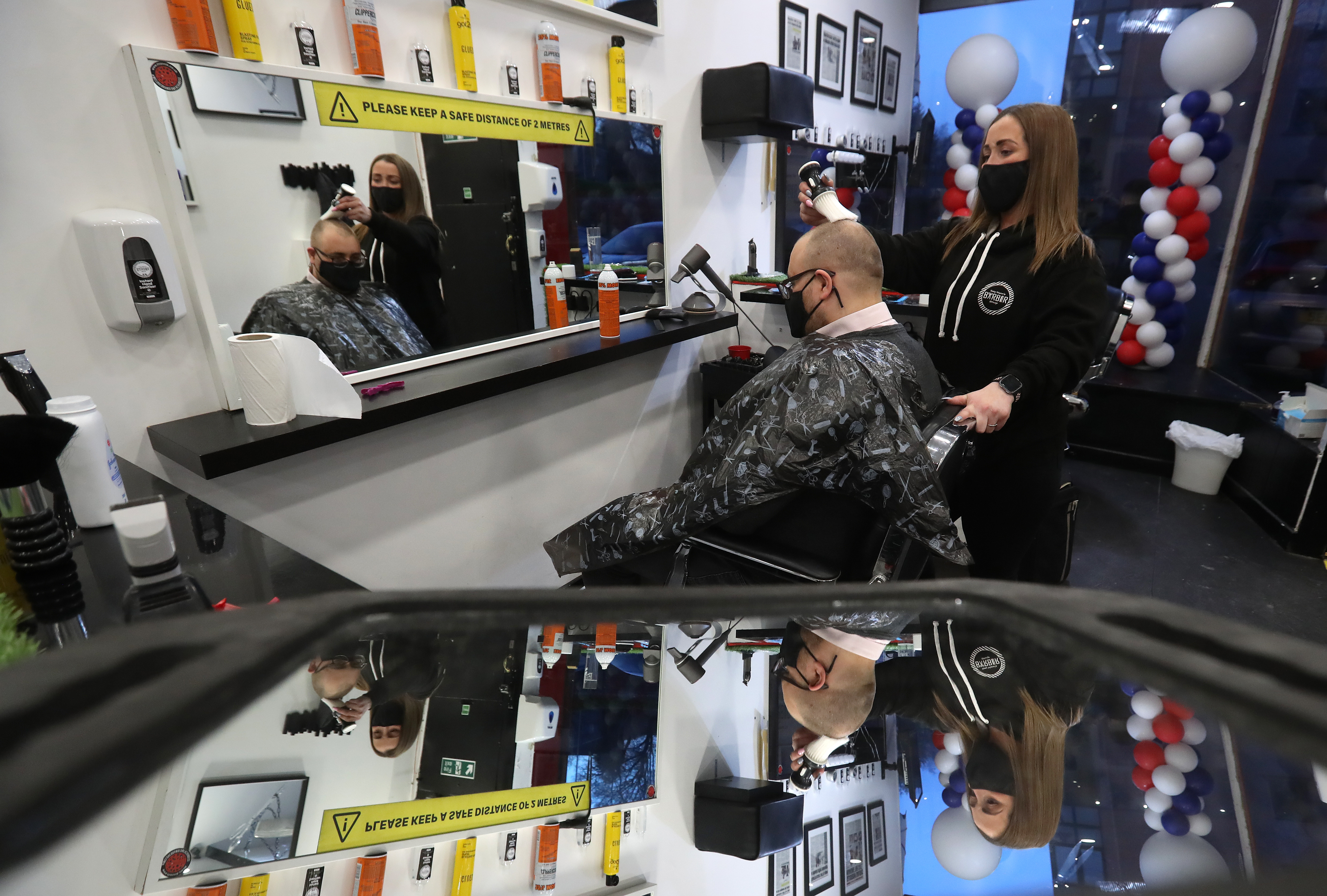 <p>Barber Maggie McGillivray trims Sam Rosenblom's hair at Tony Mann's Barber Shop in Giffnock near Glasgow as barbers reopen across Scotland. Picture date: Monday April 5, 2021.</p>